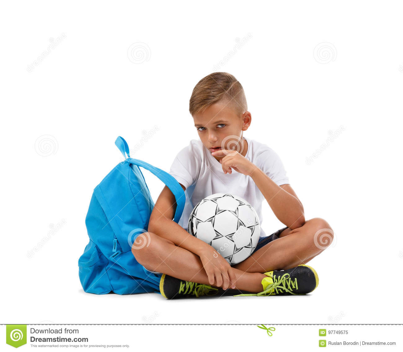 A meditative boy sitting on the ground in the lotus position. A kid with soccer ball isolated on a white background.
