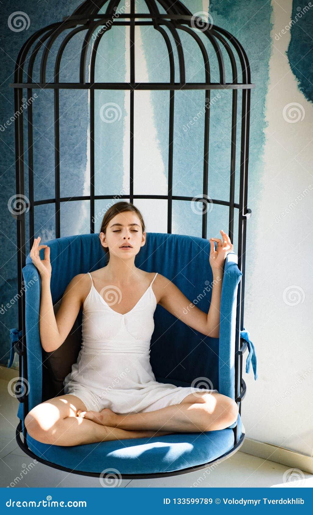 Meditativt och stillsamt Gullig kvinnakoncentrat och att meditera i stol Kvinnan kopplar av i lotusblommaposition hemma nätt