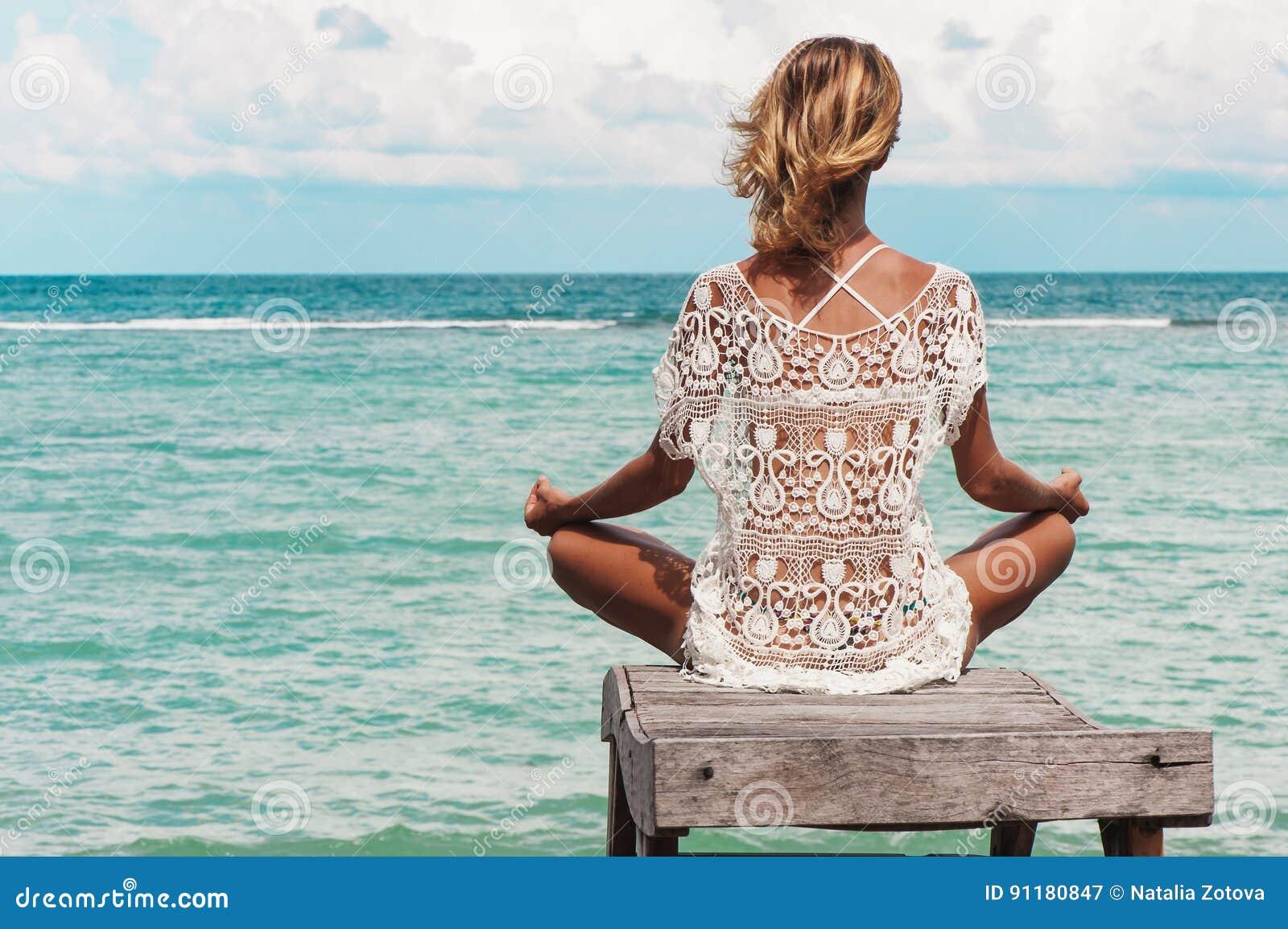 Meditazione della donna in una posa di yoga alla spiaggia - Alla colorazione della spiaggia ...