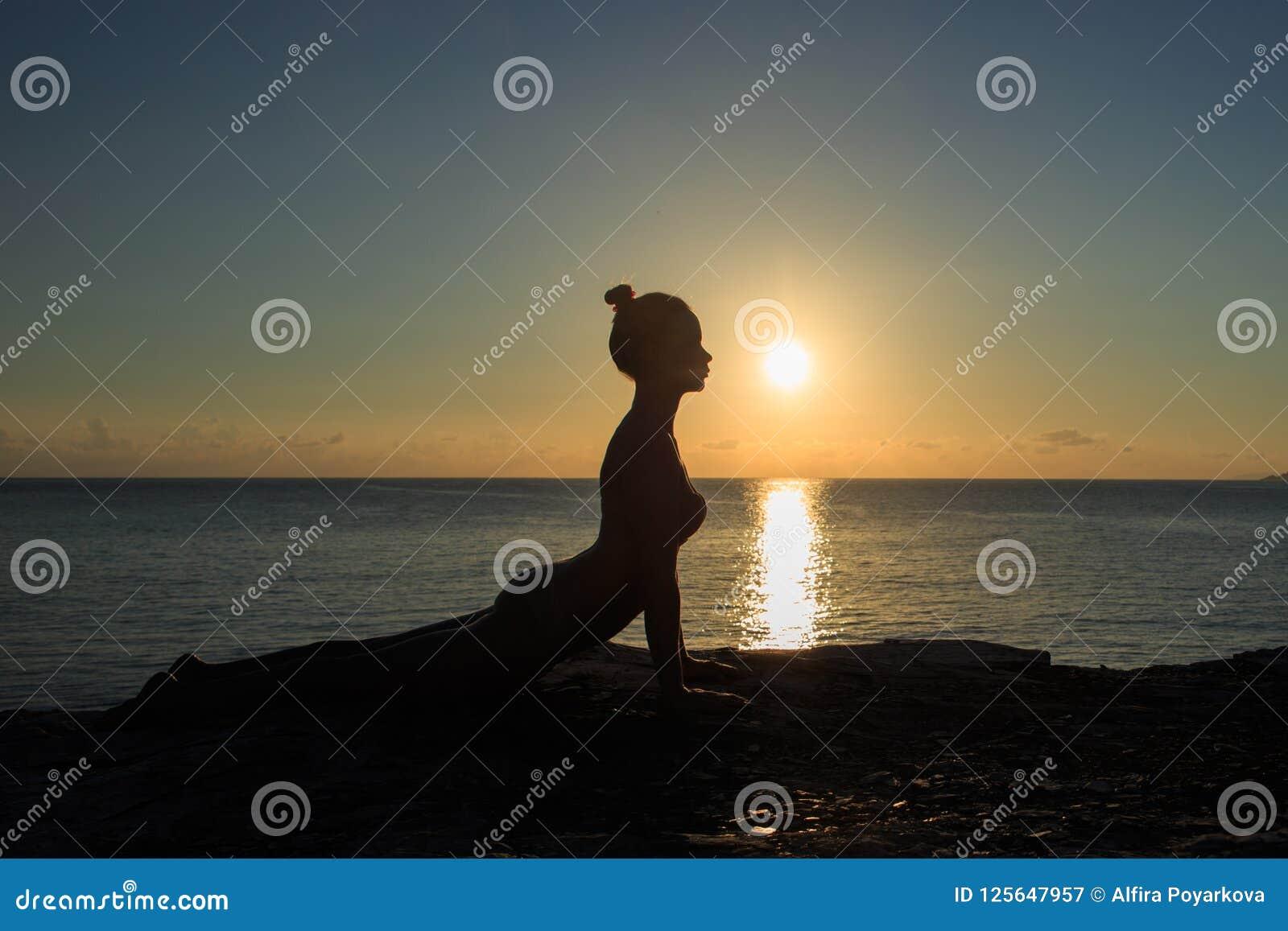 Meditazione sana della donna di yoga alla spiaggia di alba