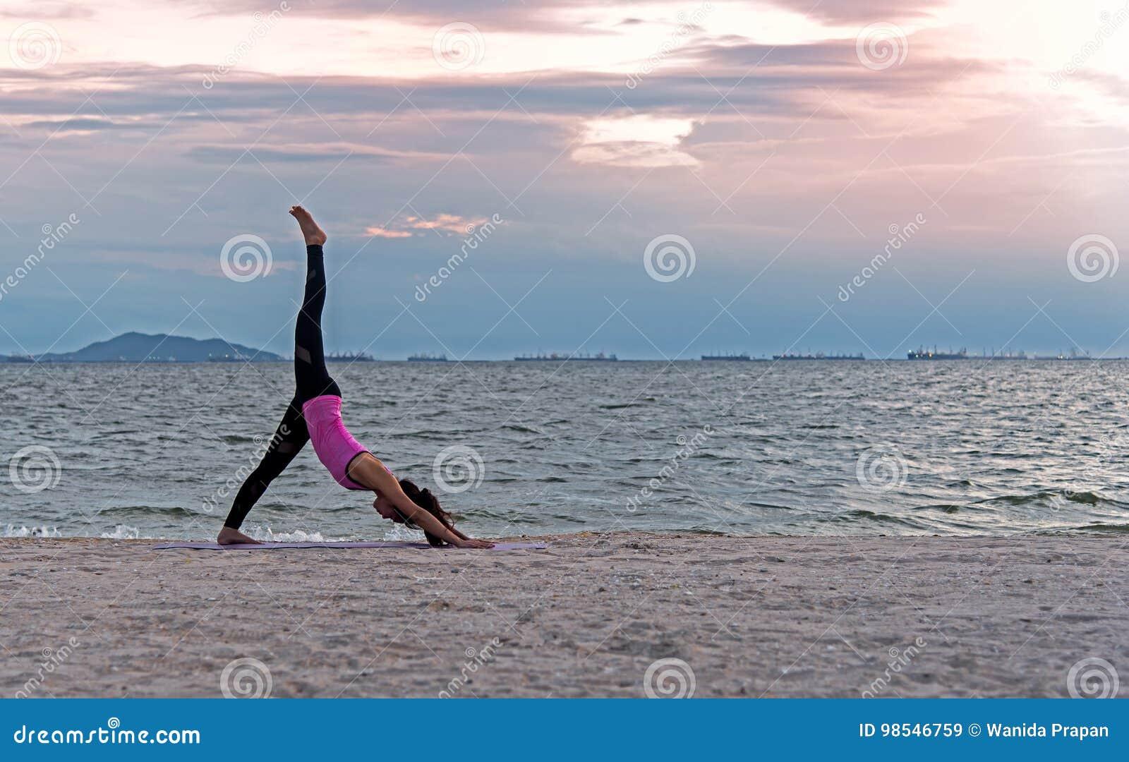 Mediterar att öva för livsstil för ung kvinna för kontur som är livsviktigt, och den praktiserande yogabollen på stranden på soln
