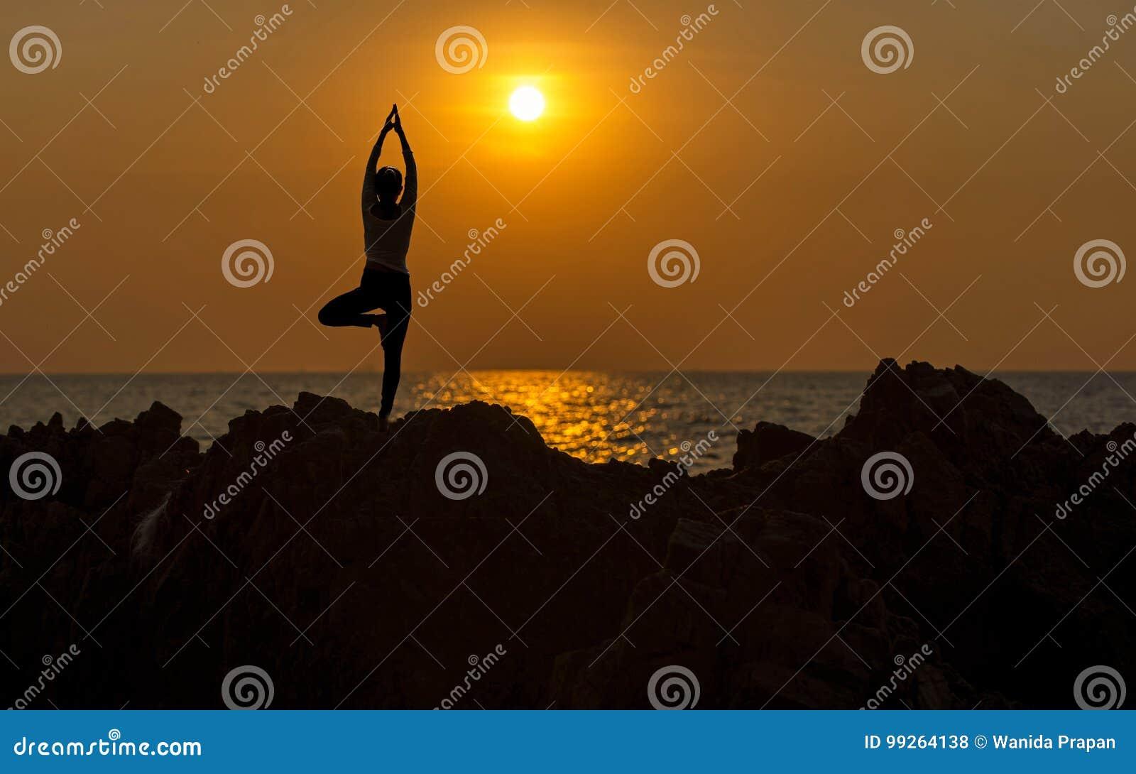 Mediterar att öva för livsstil för ung kvinna för kontur som är livsviktigt, och praktiserande yoga på stranden på solnedgången