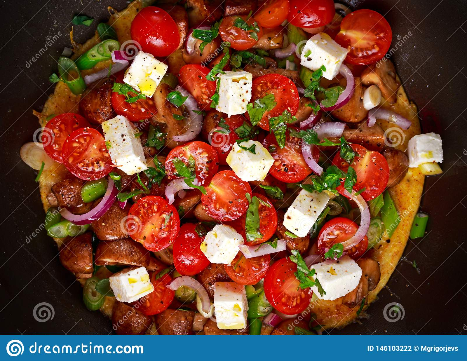 Mediterrane stijlomelet in pan met feta-kaas, kersentomaten, rode uien, paddestoelen, de lenteuien en peterselie