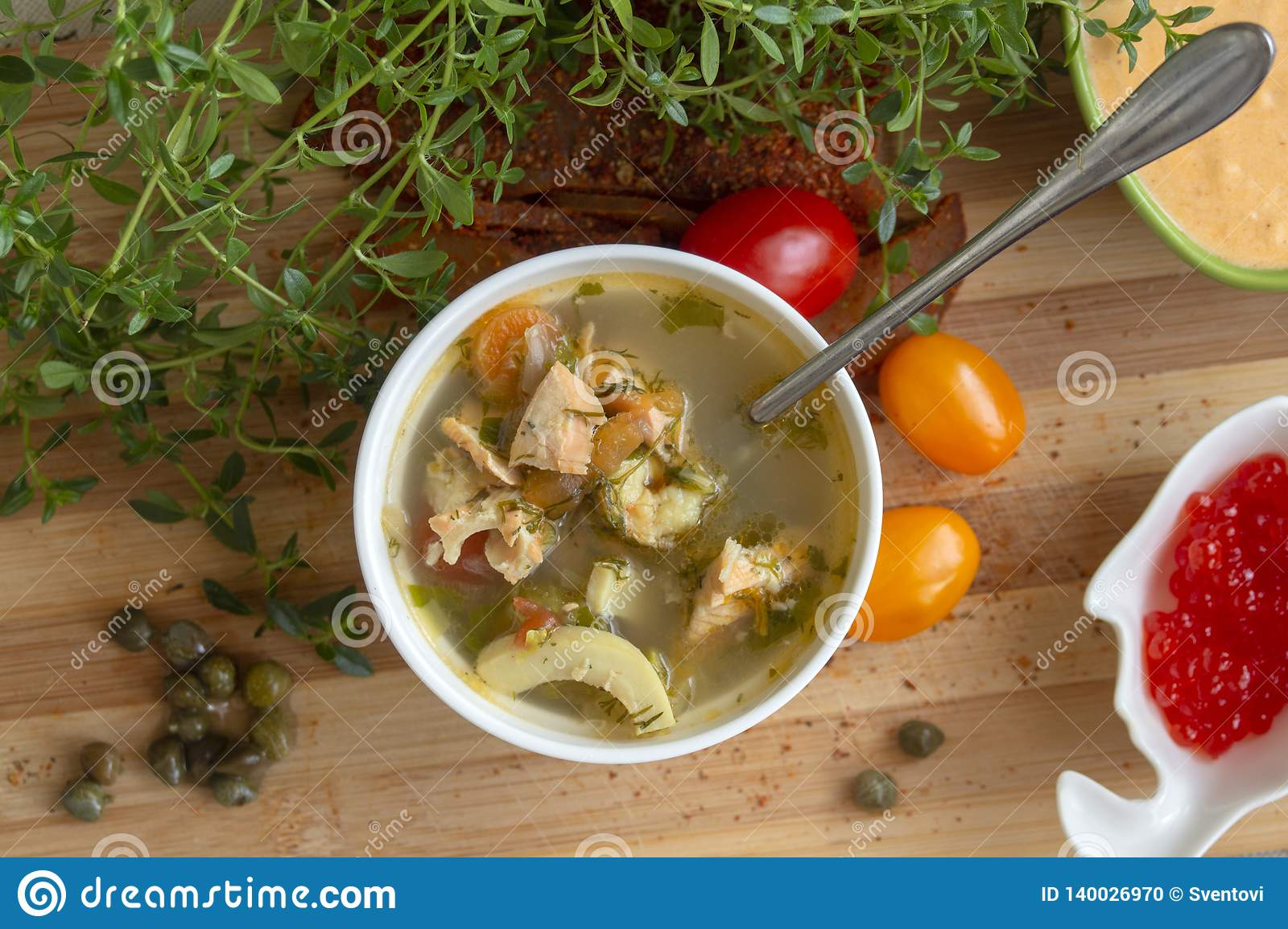 Mediterranean soup with vegetables, salmon, squid and shrimp.