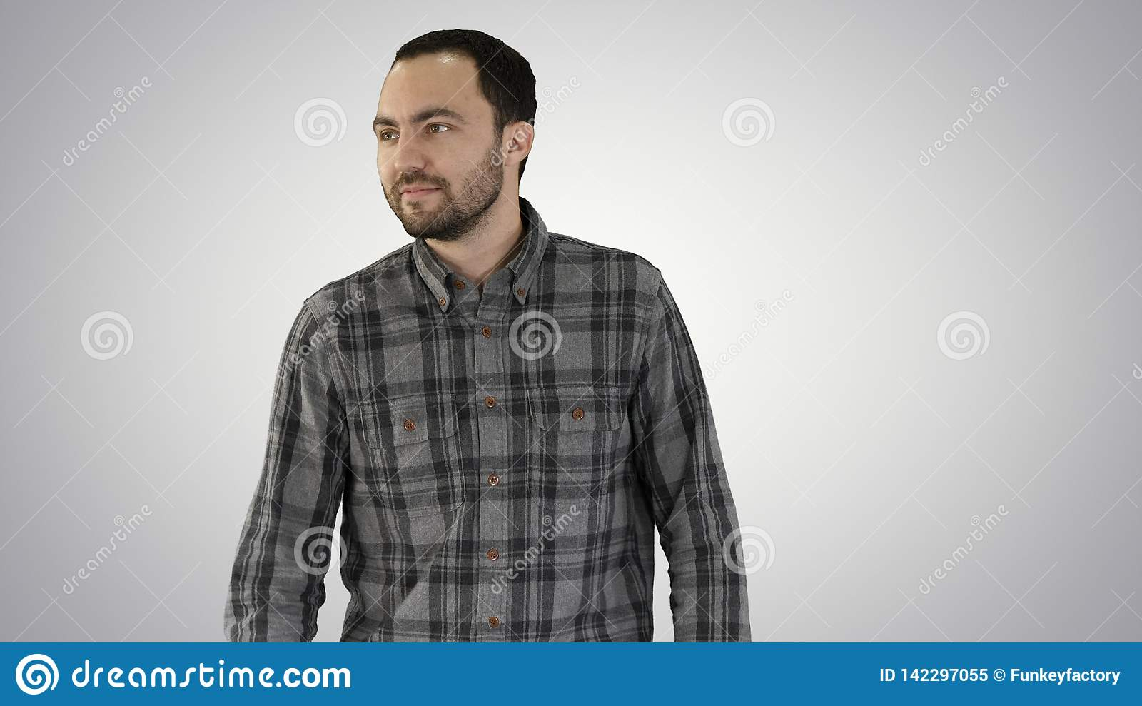 Charming successful young entrepreneur in walking and looking to the sides on gradient background.