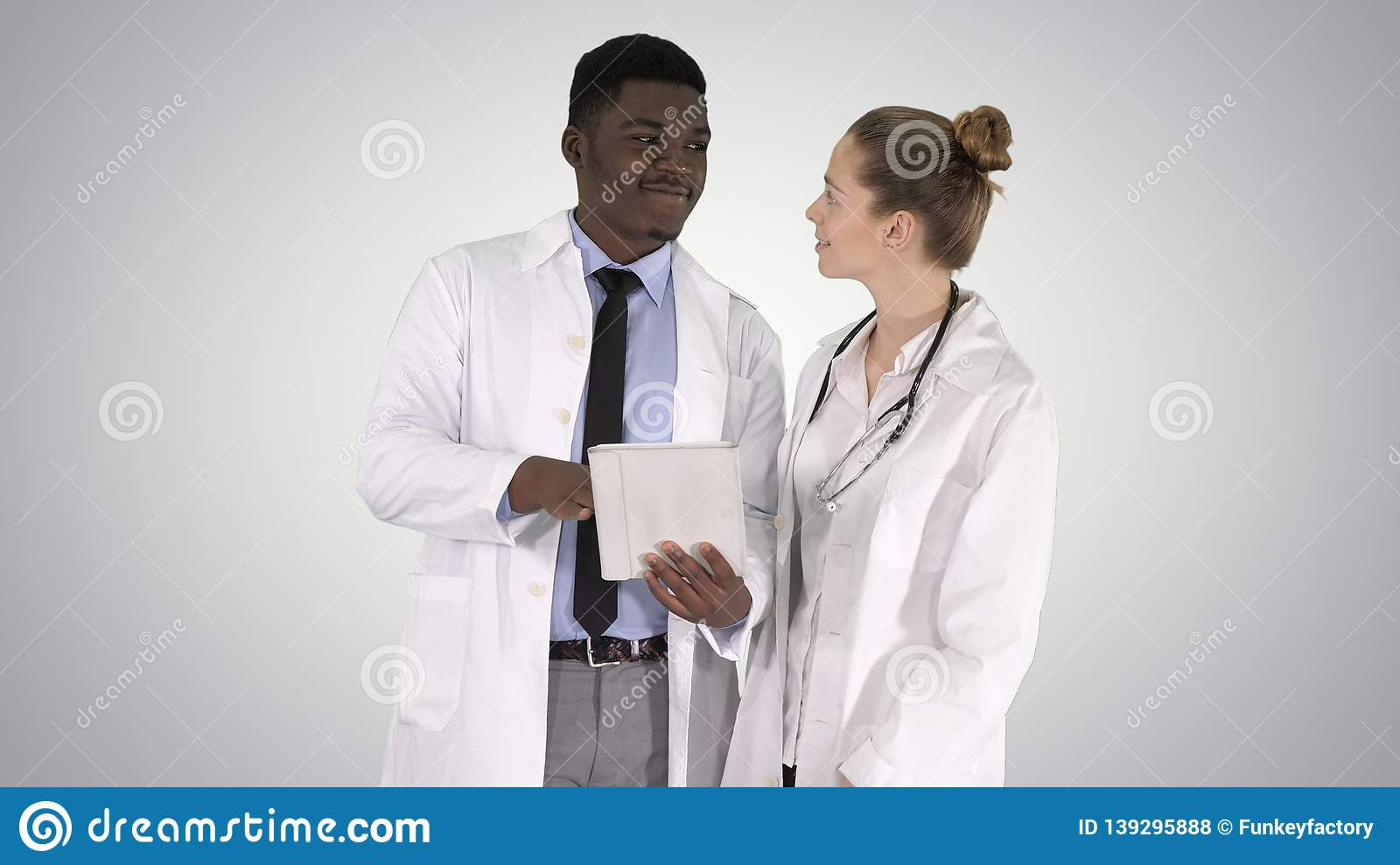 Intellectual healthcare professional afro american doctor with collegue using digital tablet on gradient background.