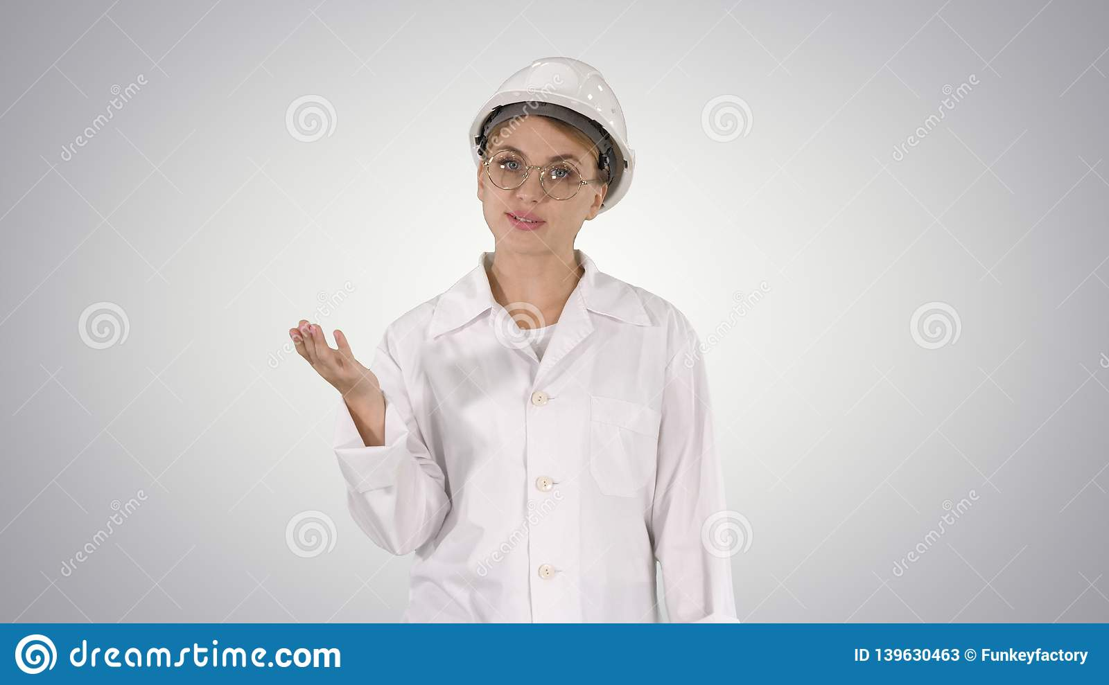Mature engineer woman in hard hat and lab coat talking and presenting something pointing to sides on gradient background