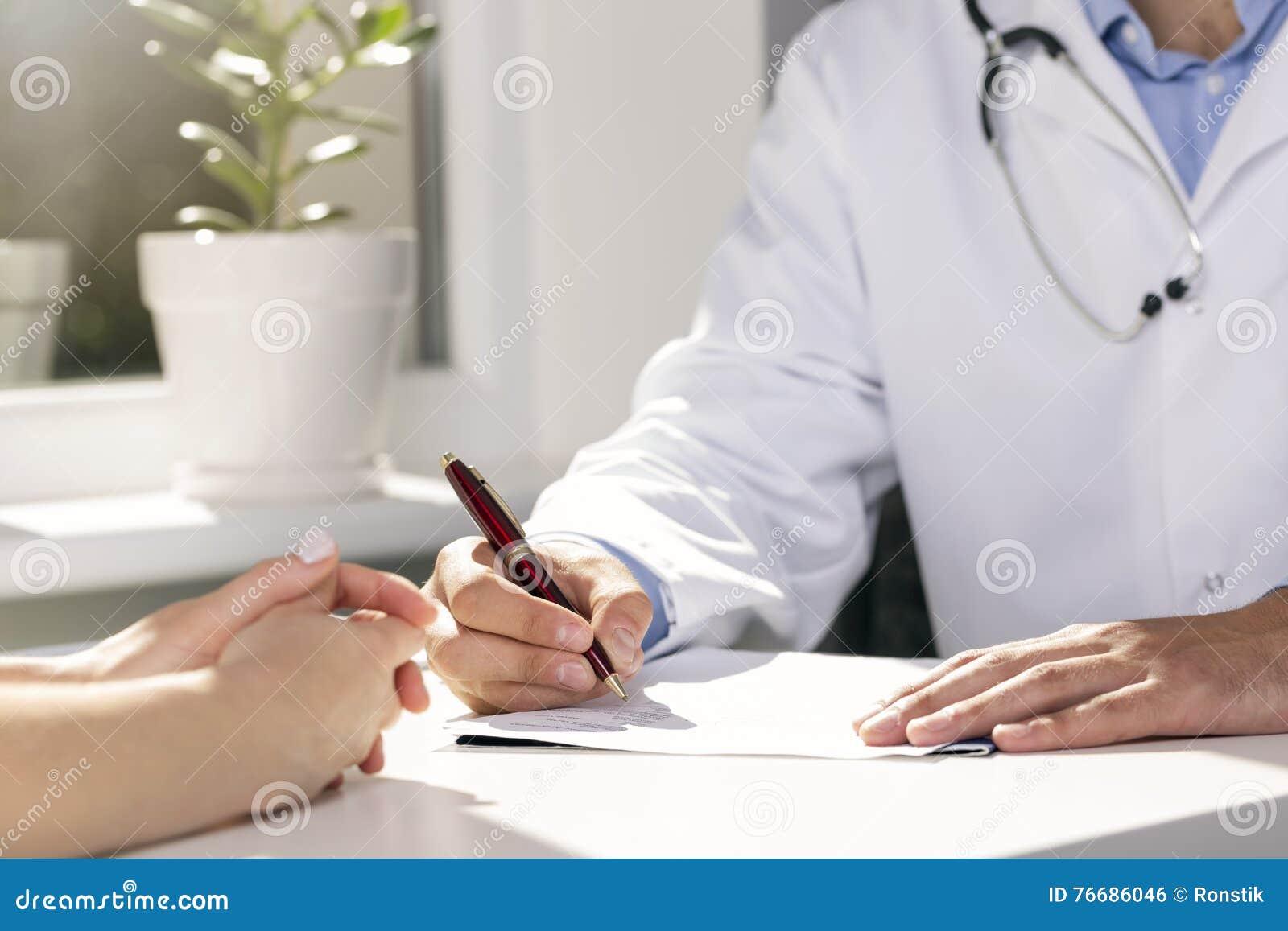Medizinische Beratung - Doktor und Patient, die durch die Tabelle sitzen