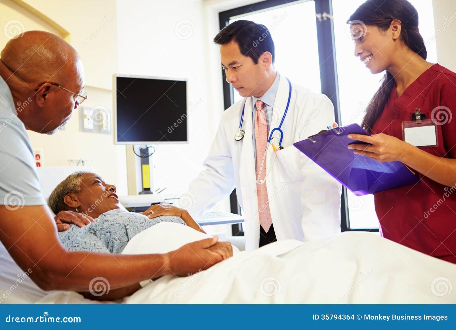 Medizinischer Team Meeting With Senior Couple im Krankenhauszimmer