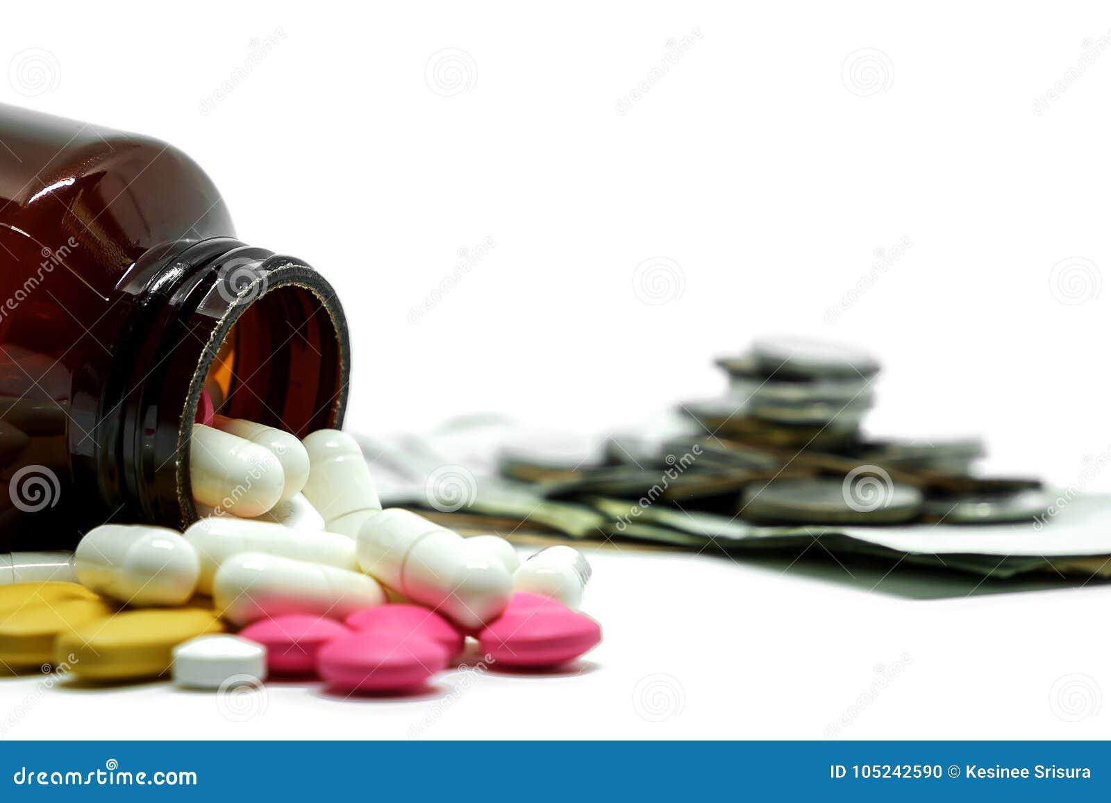 Medizinpillen, Vitamine und Flasche auf unscharfer Geldmünze und weißer Hintergrund mit Kopienraum