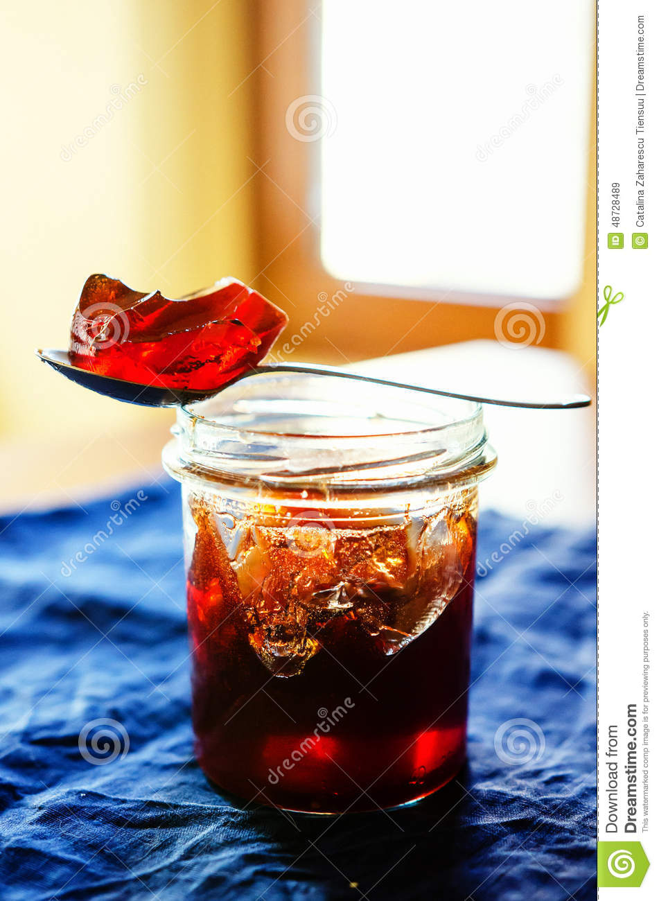 Medlar jelly in a jar and a piece of jelly in the spoon.