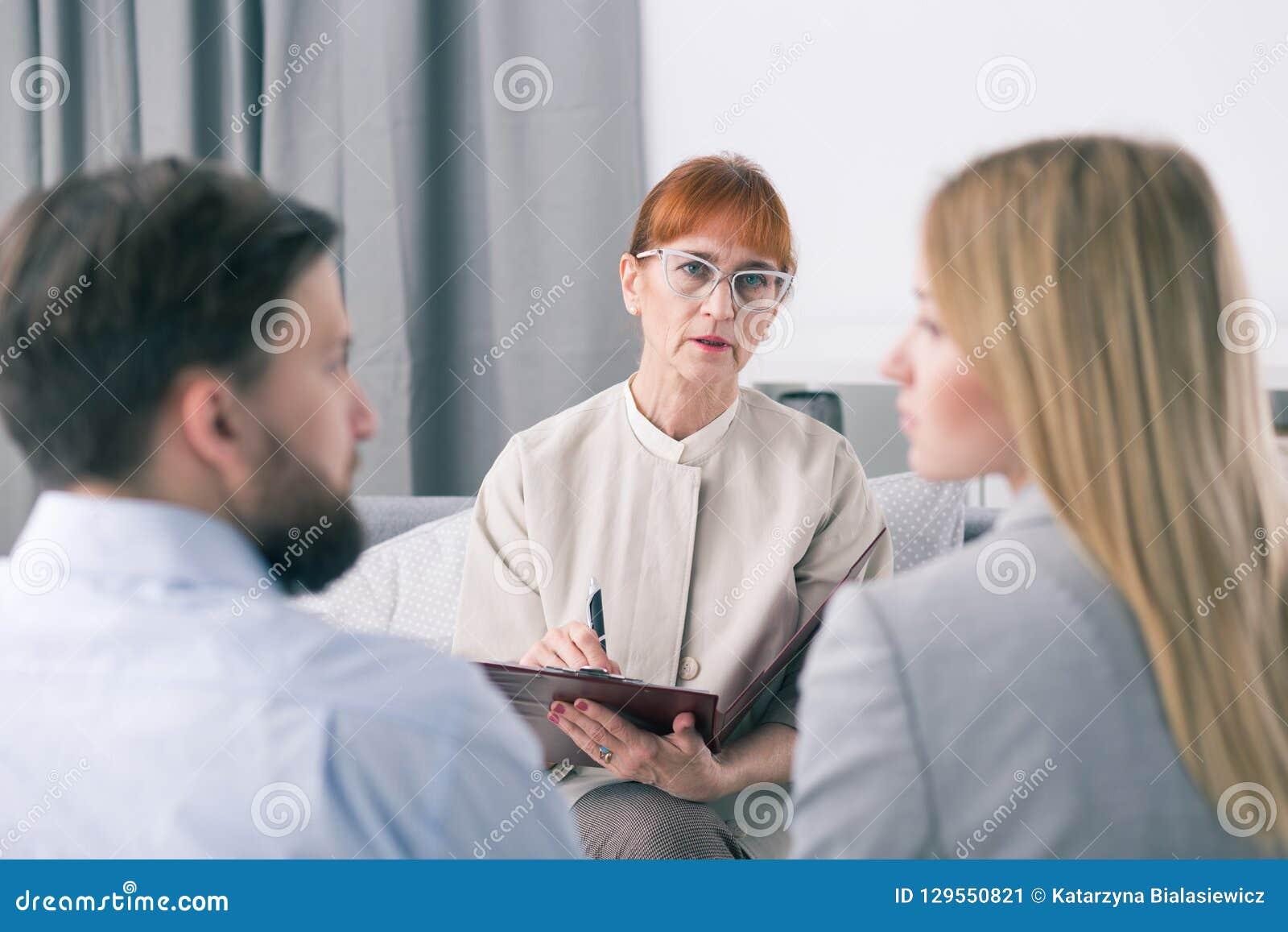 Medlare som talar till ett par under en period