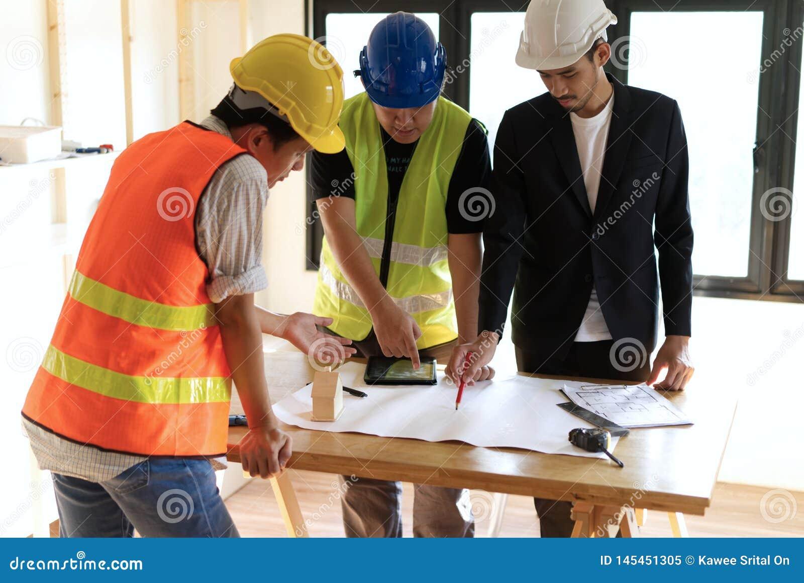 Medlemmar för hem- byggnad som samlar på arbetetabellen som har någon diskussion för projektplanläggning