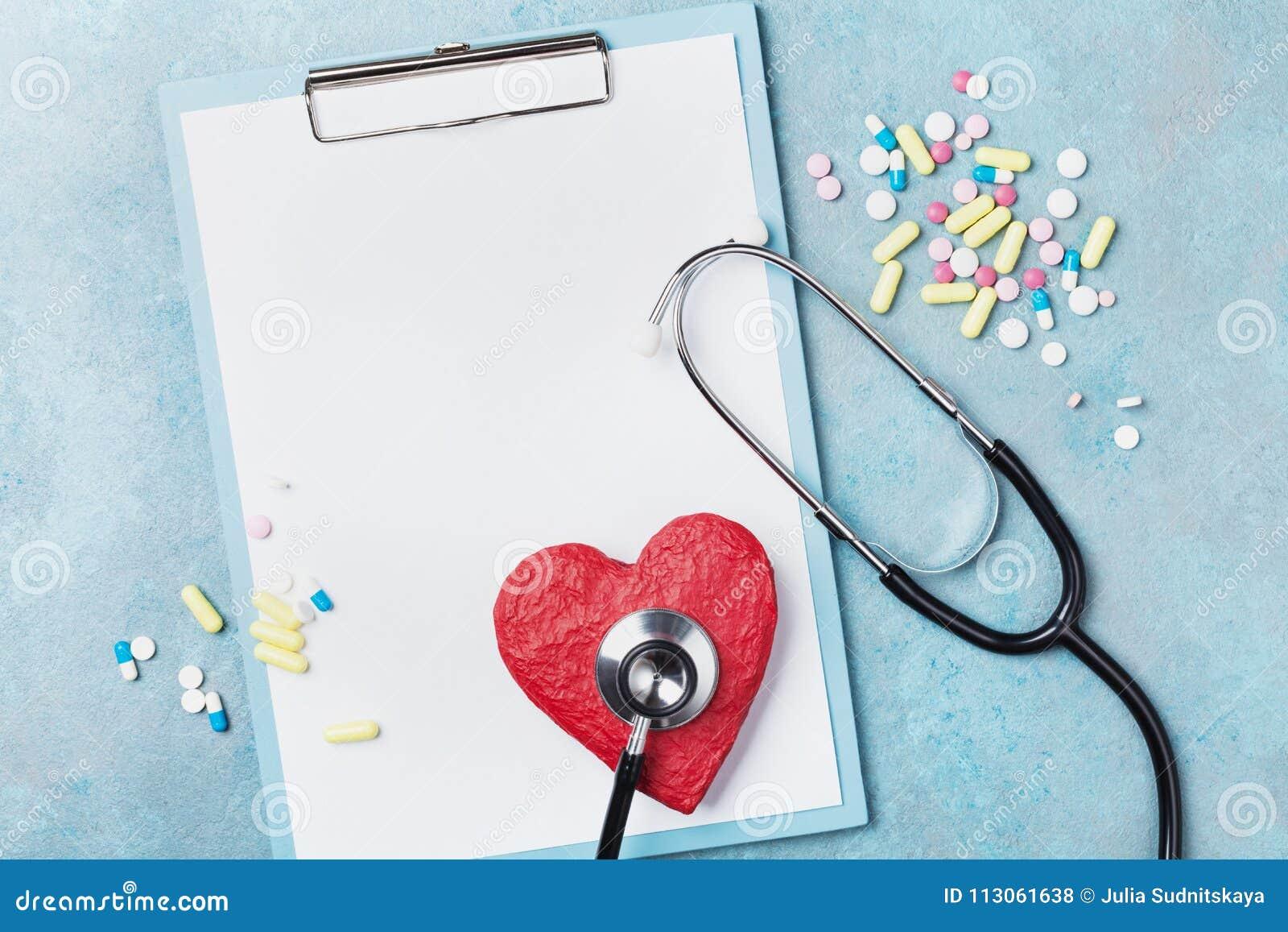 Medycyna schowek, stetoskop, lek pigułki i czerwony kształt serce na błękitnego tła odgórnym widoku, Zdrowy i kardiologia pojęcie