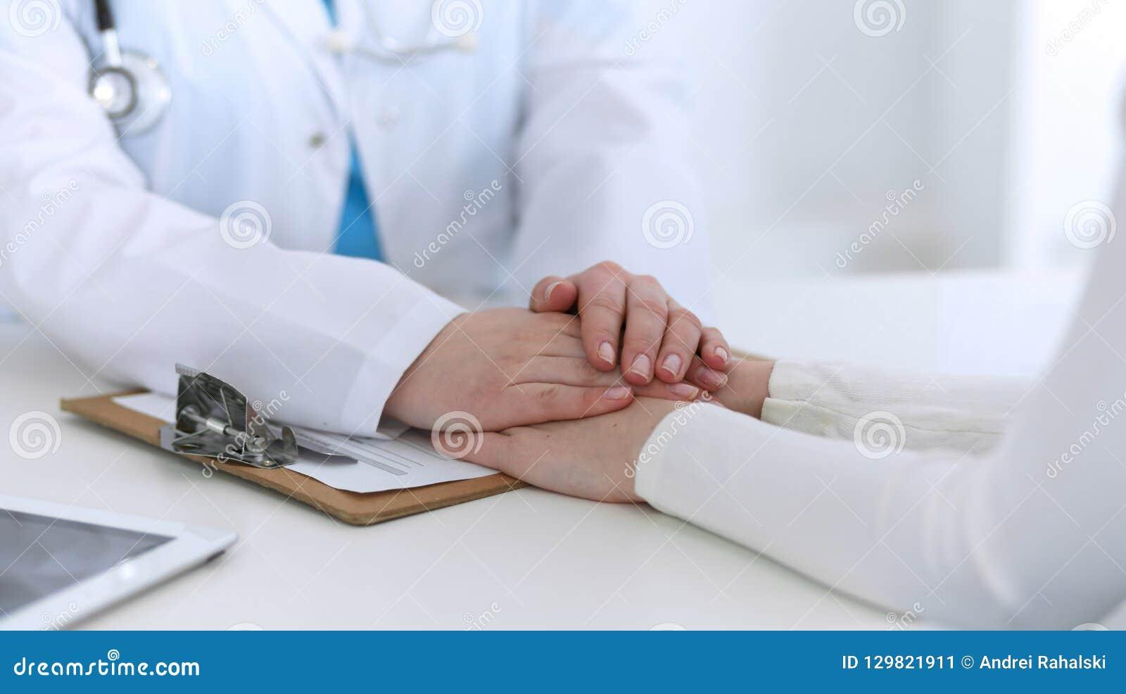 Medycyny lekarki ręka reasekuruje jej żeńskiego cierpliwego zbliżenie Medycyna pociesza pojęcie w opiece zdrowotnej i ufa,