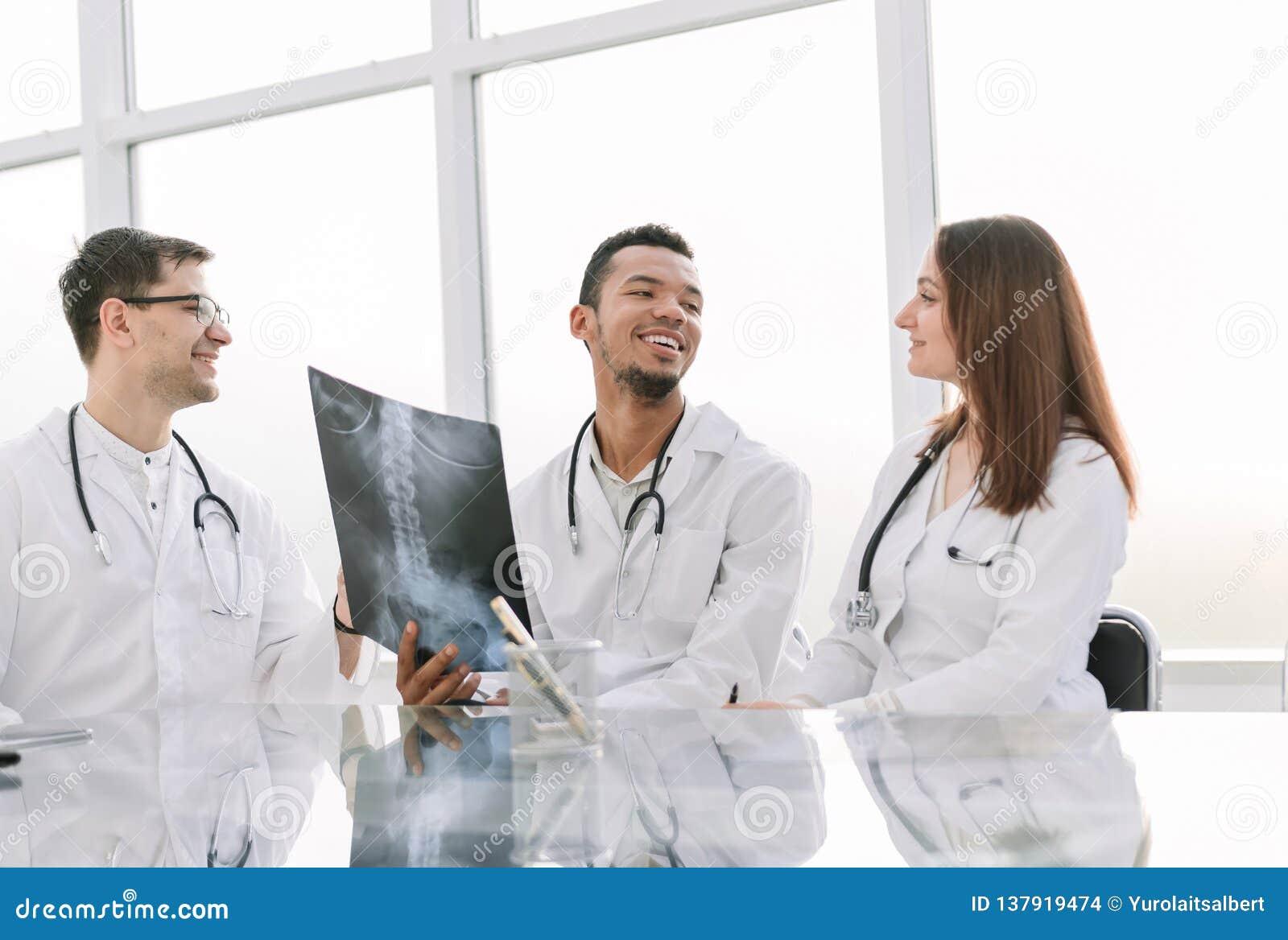 Medyczni koledzy dyskutują promieniowanie rentgenowskie, siedzi przy biuro stołem