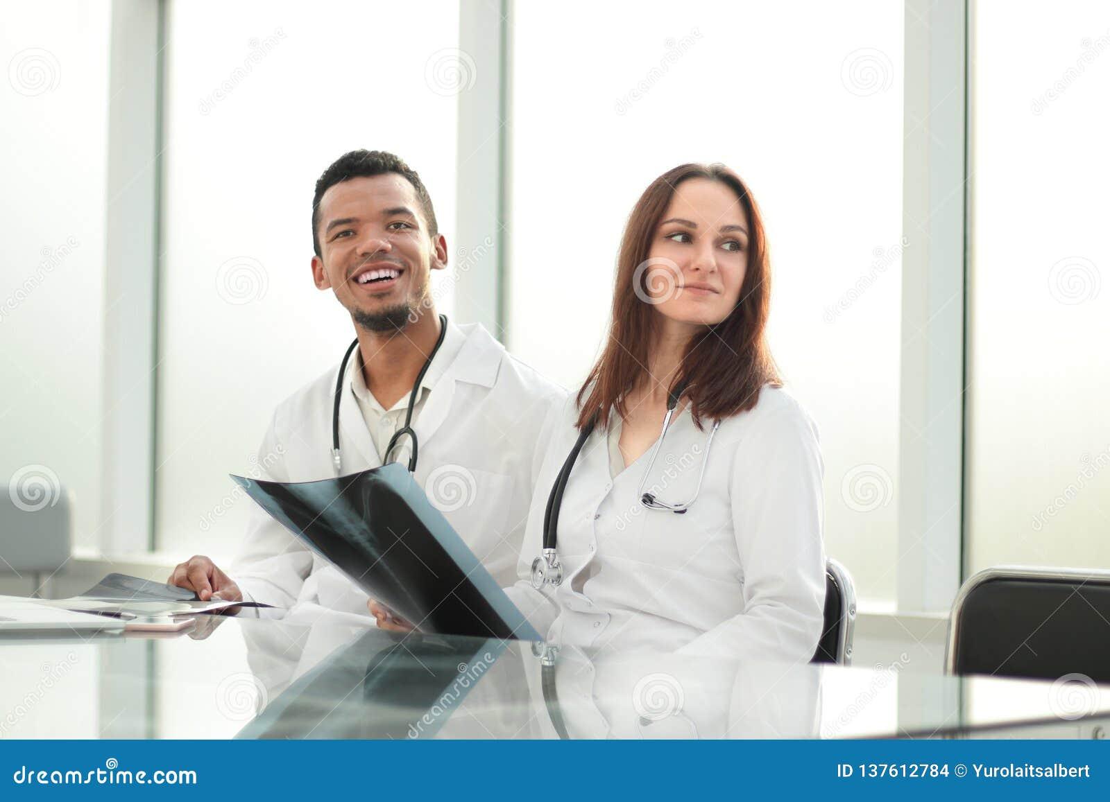 Medyczni koledzy z promieniowania rentgenowskiego obsiadaniem przy biurowym biurkiem