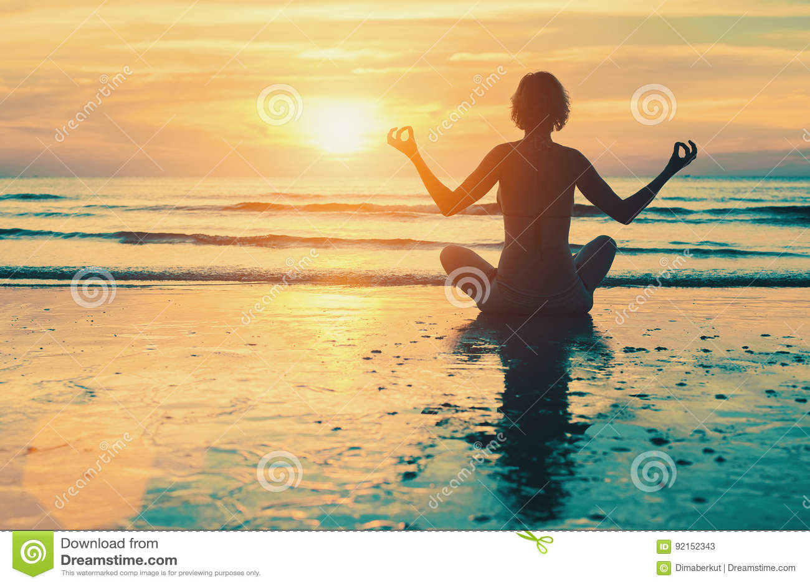 Medytaci dziewczyna na morzu podczas zmierzchu