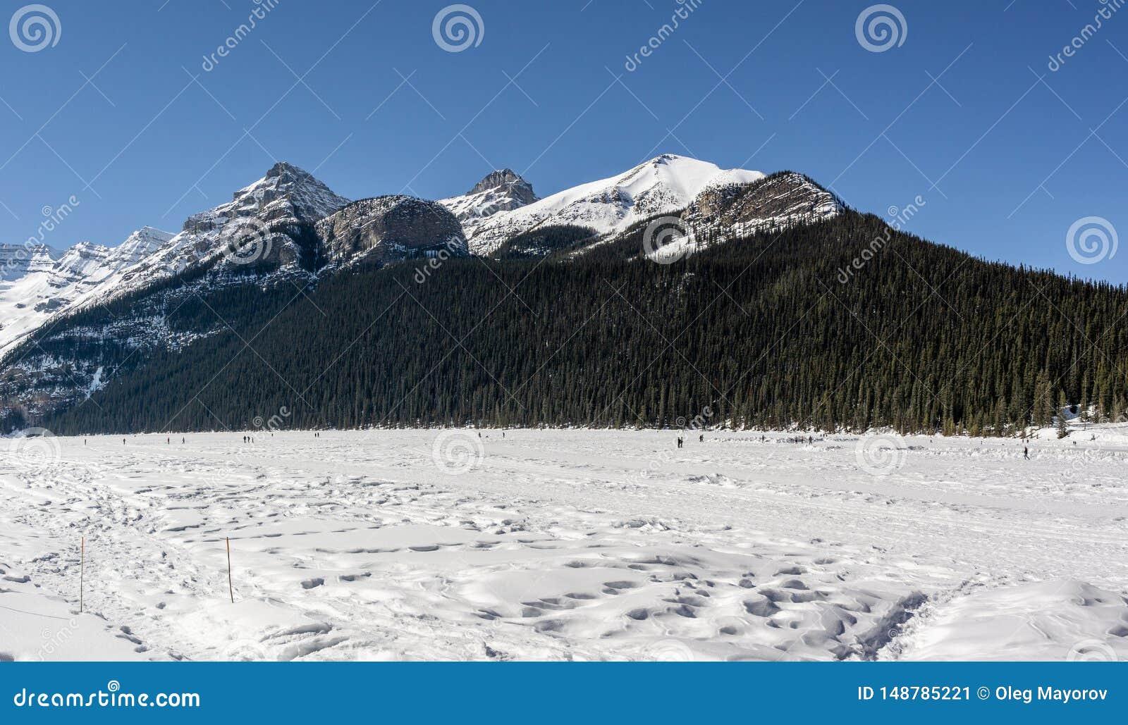 Meer Louise, CANADA - MAART 20, 2019: bevroren meer en bergen met sneeuwpieken
