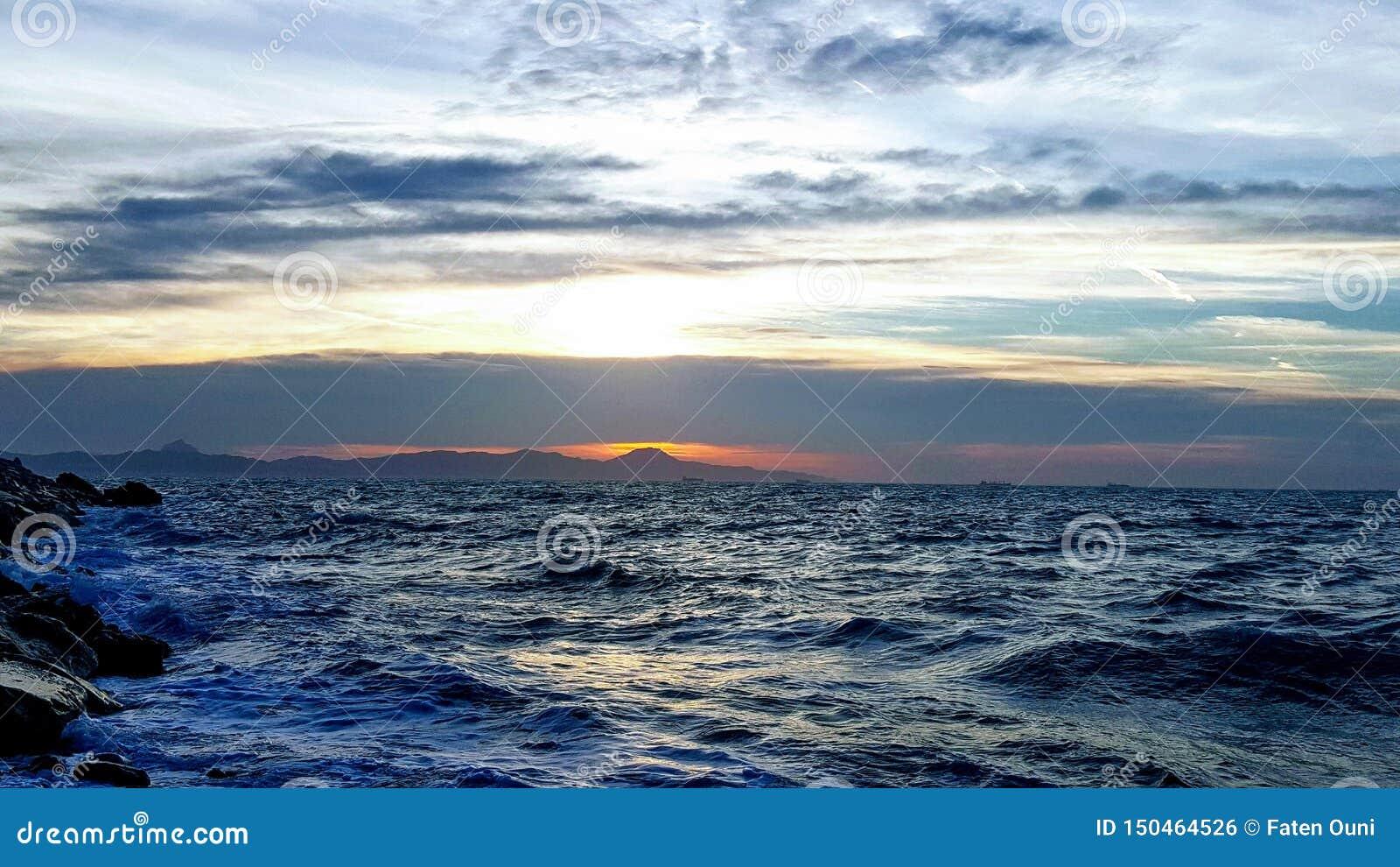 Meer schaut verärgerten Himmel mit Sonnenuntergang hinten