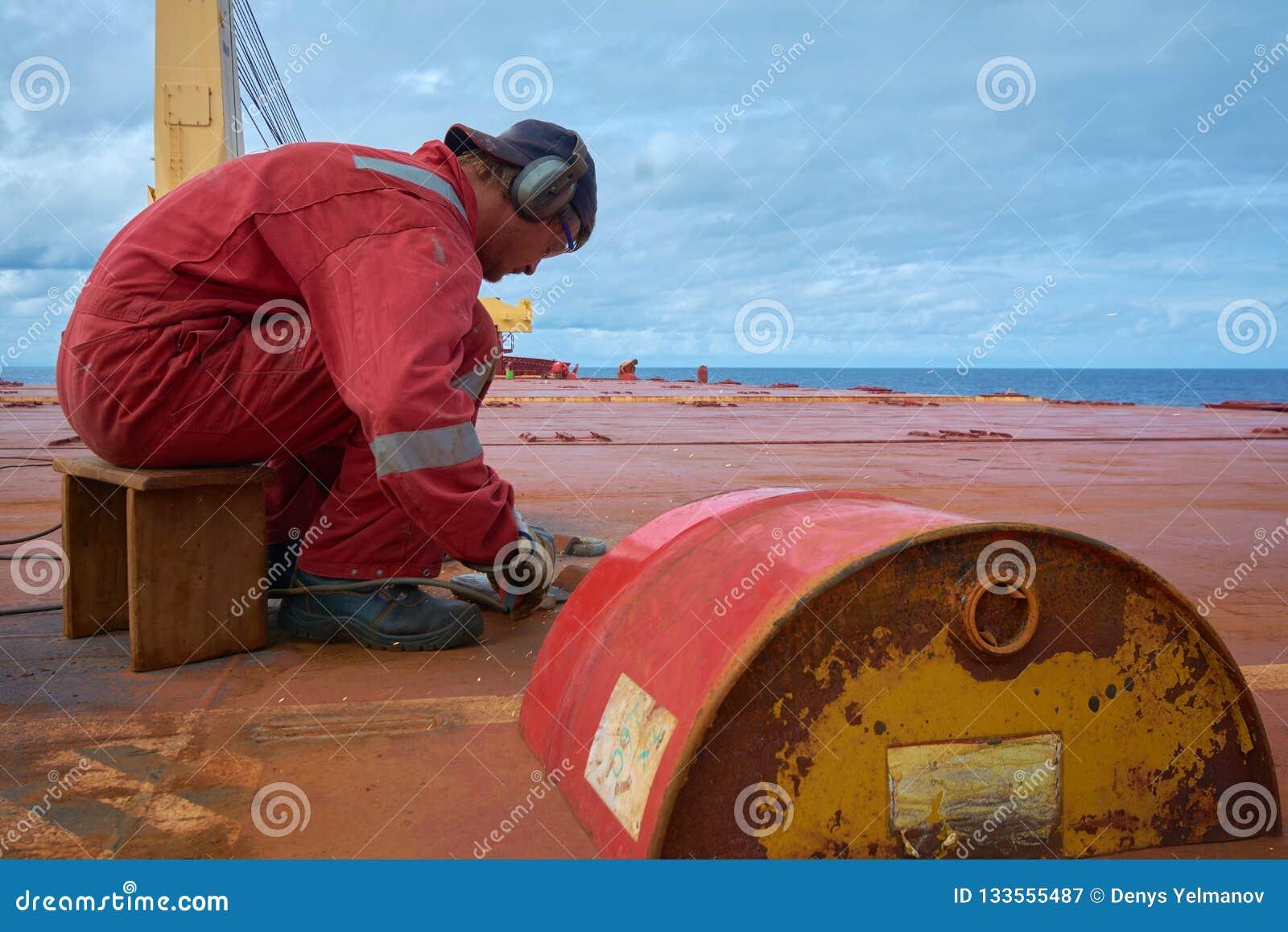 An meeres- circa im Oktober 2018: Seeleute, die alte D-Clips an der offenen Plattform eines Schiffs schneiden SchiffsWartungskonz
