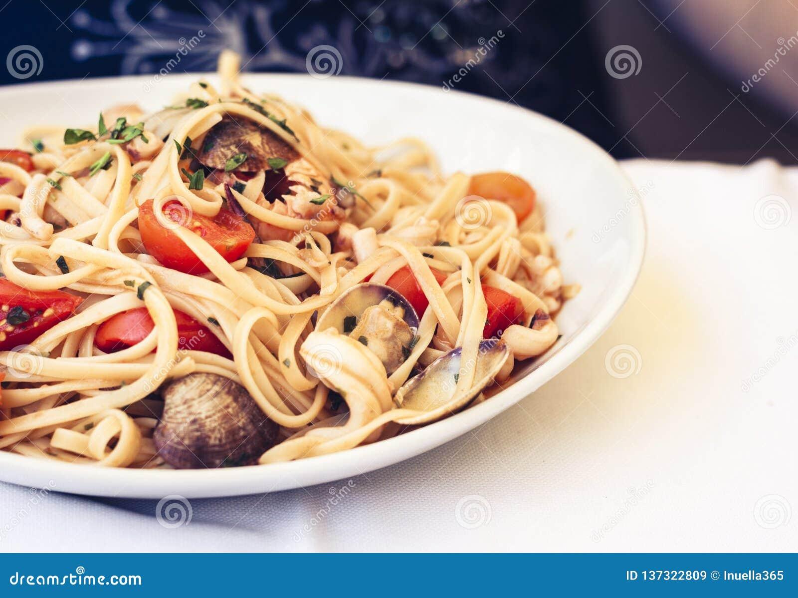 Meeresfrüchteteigwarenspaghettis Linguine-Wunschmiesmuscheln, Muscheln, Kirschtomaten, frischer Parmesankäse auf der weißen Platt