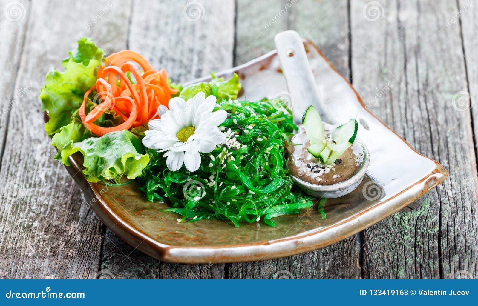 Meerespflanzen-Salat wakame in der Platte mit Essstäbchen auf Bambusmatte Japanische Küche - gesunde Meeresfrüchte