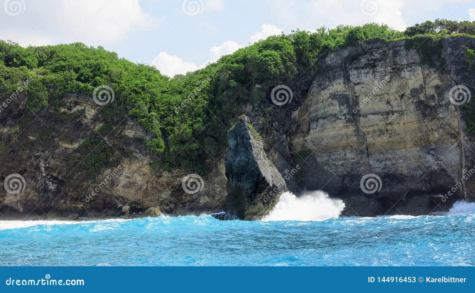 Meereswellen, die auf einem Felsen im Meer nahe der felsigen Küste von Insel Nusa Penida in Indonesien brechen