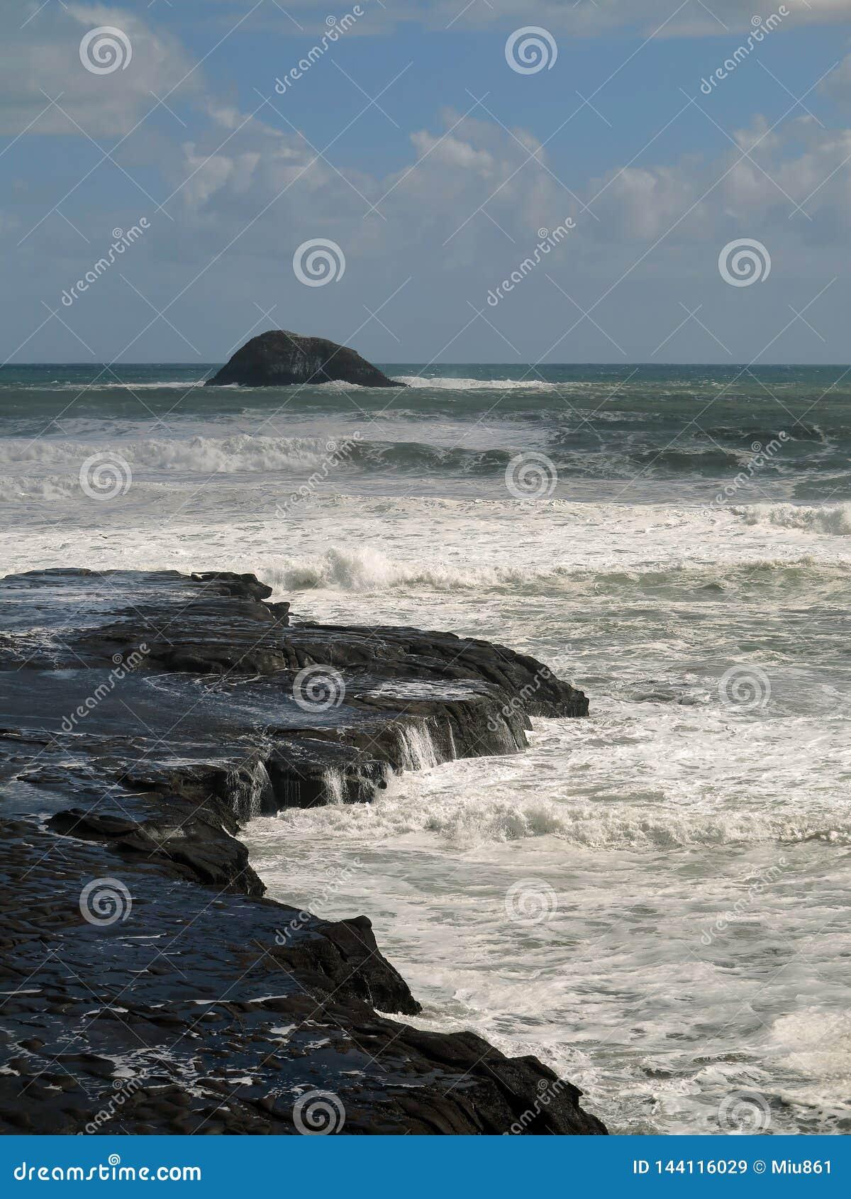 Meereswoge, der auf schwarzen Rocky Shore zusammenstößt Rocky Seacoast mit schäumenden Meereswogen