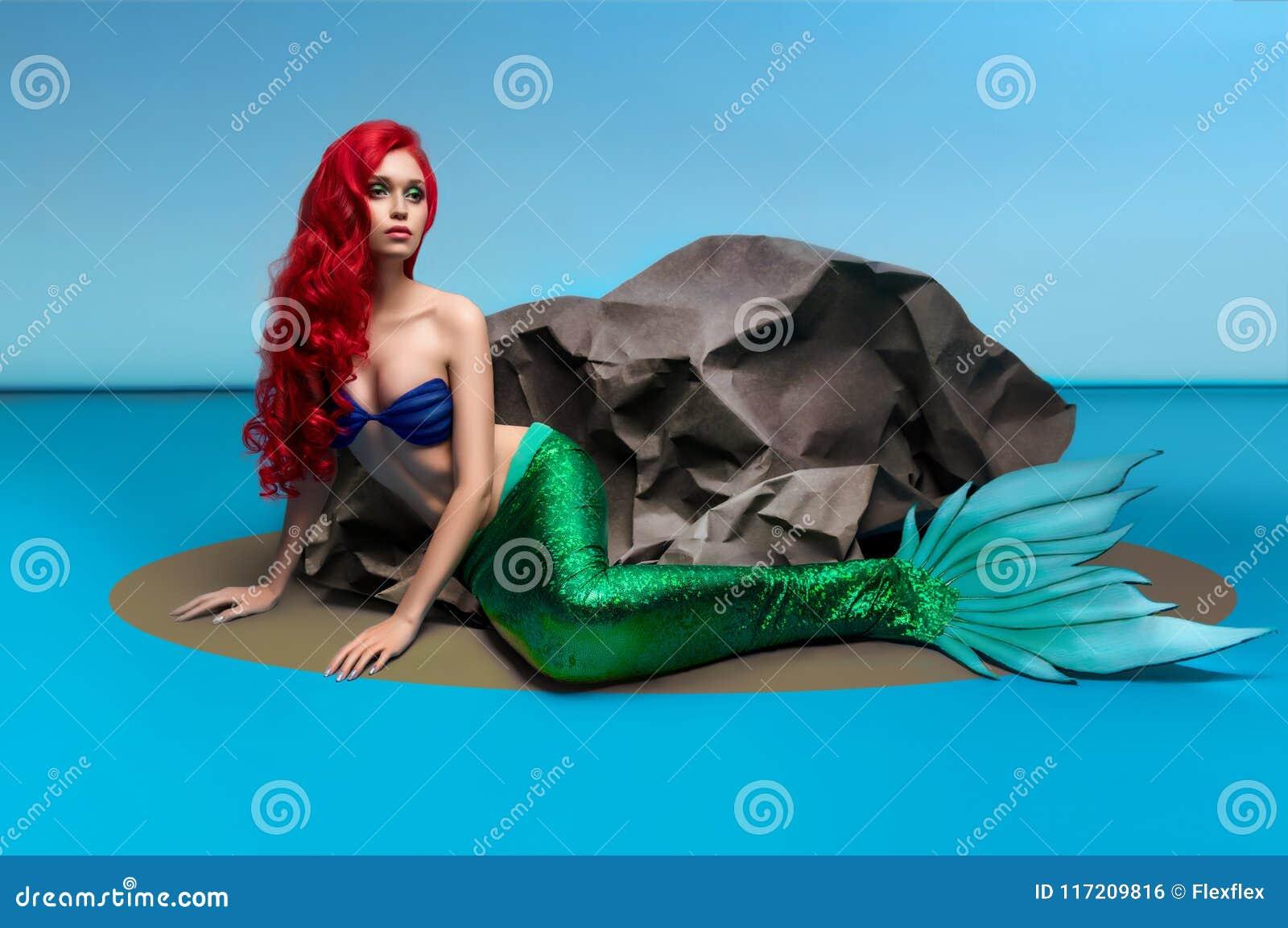 Meermin met rood haar die dichtbij steen rusten