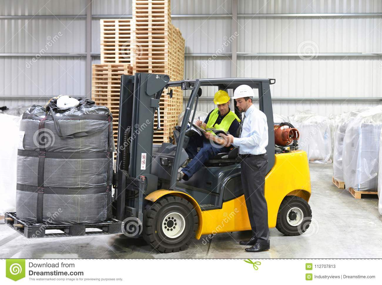 Meeting of the manager and worker in the warehouse - forklift an