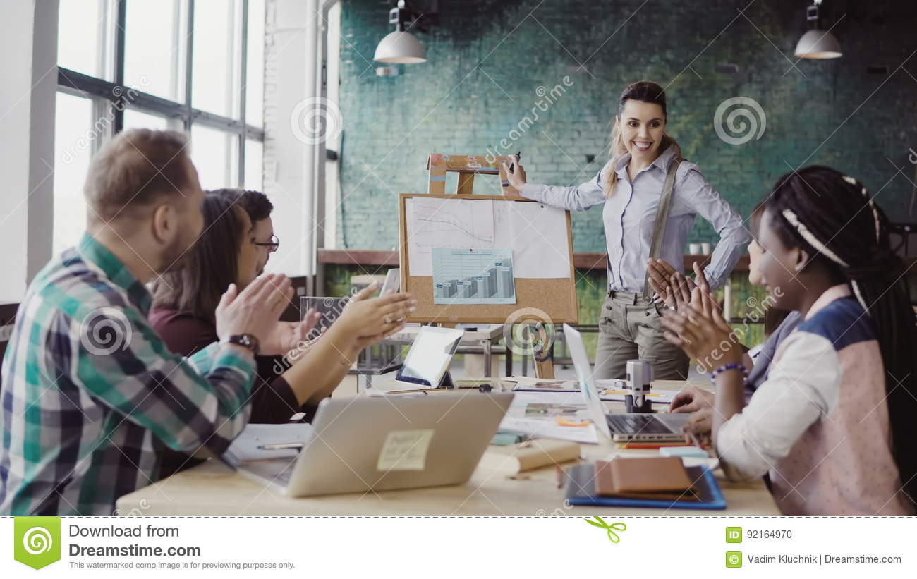 Meeting of mixed race business team at loft office. Woman manager presenting financial data, group of people clapping.