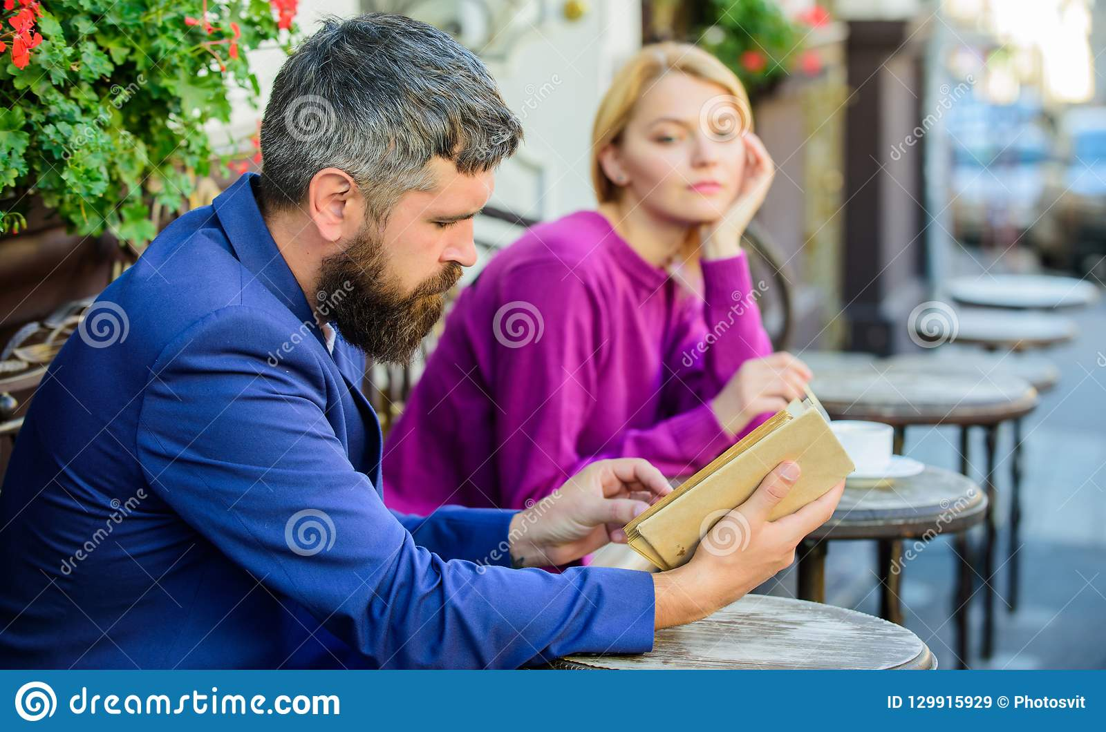 Meeting people with similar interests. Man and woman sit cafe terrace. Girl interested what he reading. Literature