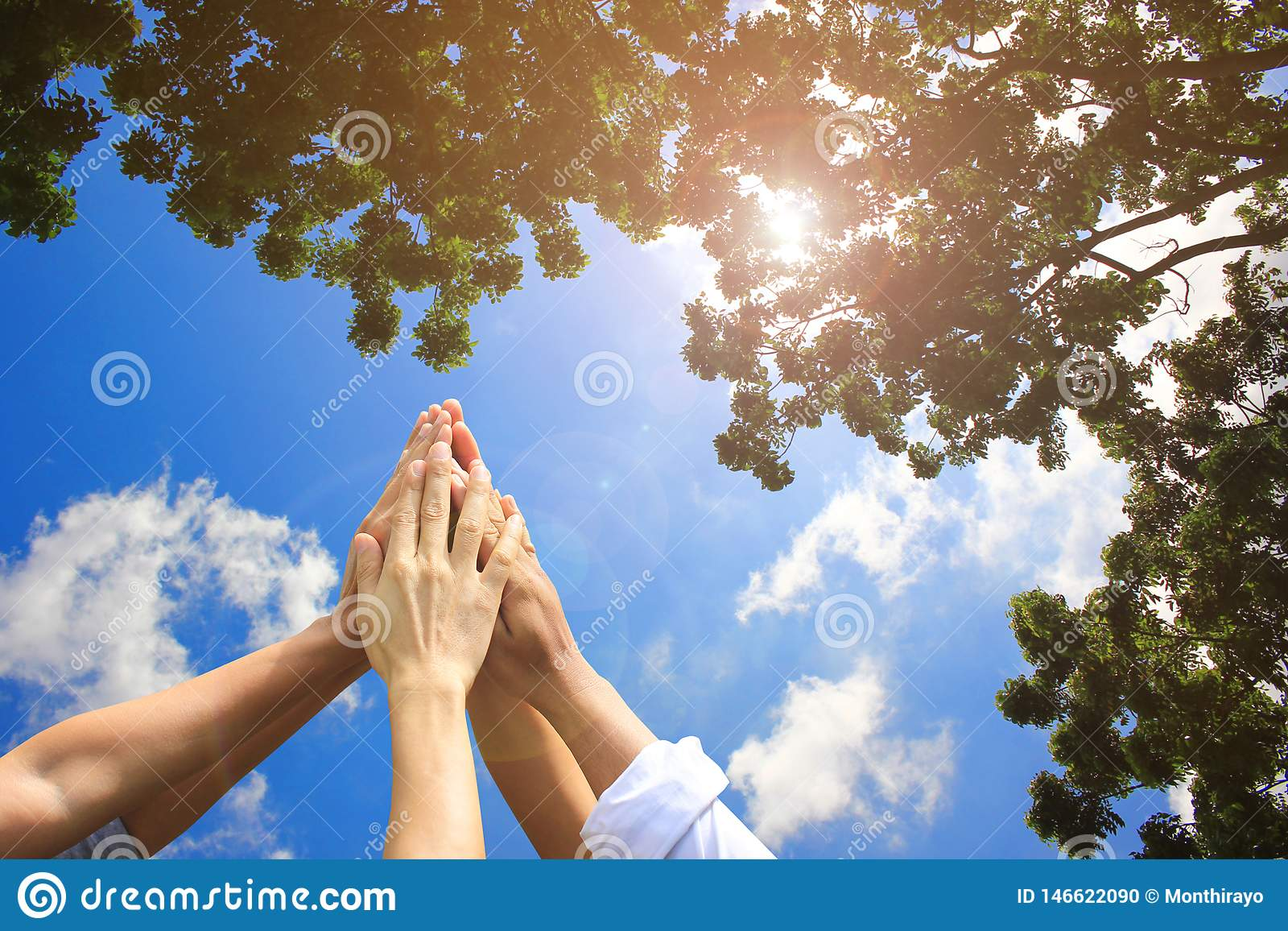 Meeting teamwork concept,Friendship,Group people with stack of hands showing unity on natural green and blue sky background