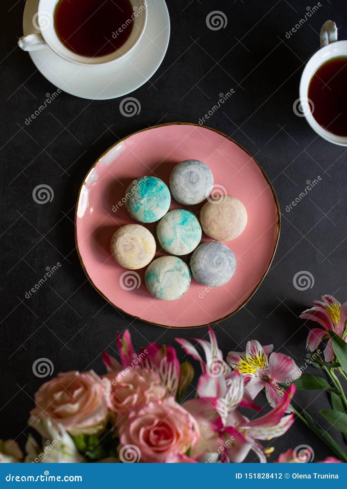 Mehrfarbige macarons auf der rosa Platte auf einer dunklen Tabelle weiße Tasse Tee oder Kaffee Frühstück mit Nachtisch Blumenstra