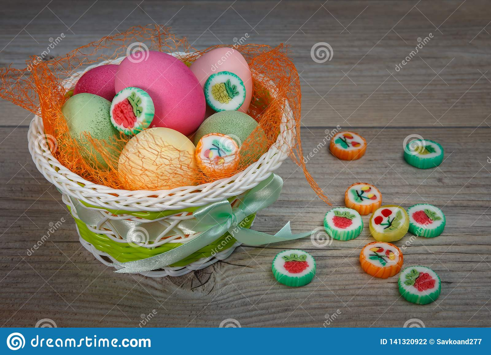 Mehrfarbige Ostereier und Bonbons in einem schönen Korb
