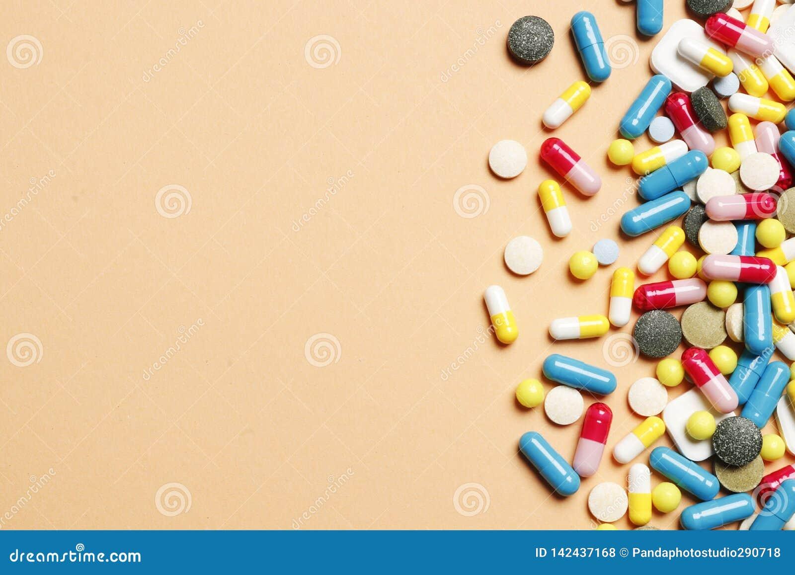 Mehrfarbige Vitamine auf einem rosa Hintergrund