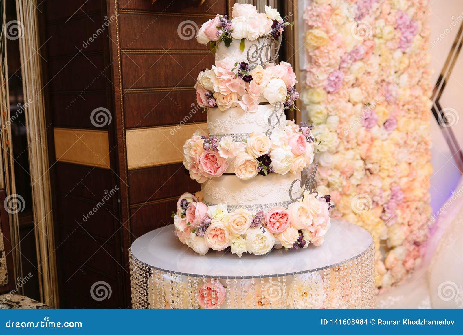 Mehrstufige Hochzeitstorte verziert mit Blumenständen auf einer Tabelle Konzept des Essens, der Bonbons und der Nachtische an ein