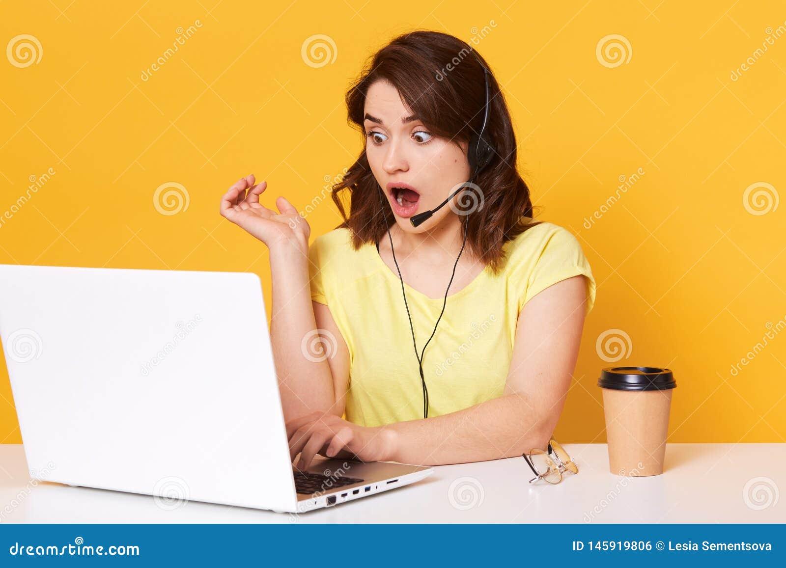 Meia foto do lengh do operador da mulher que senta-se com boca aberta, olhando a tela do laptopon, isolada sobre o fundo amarelo