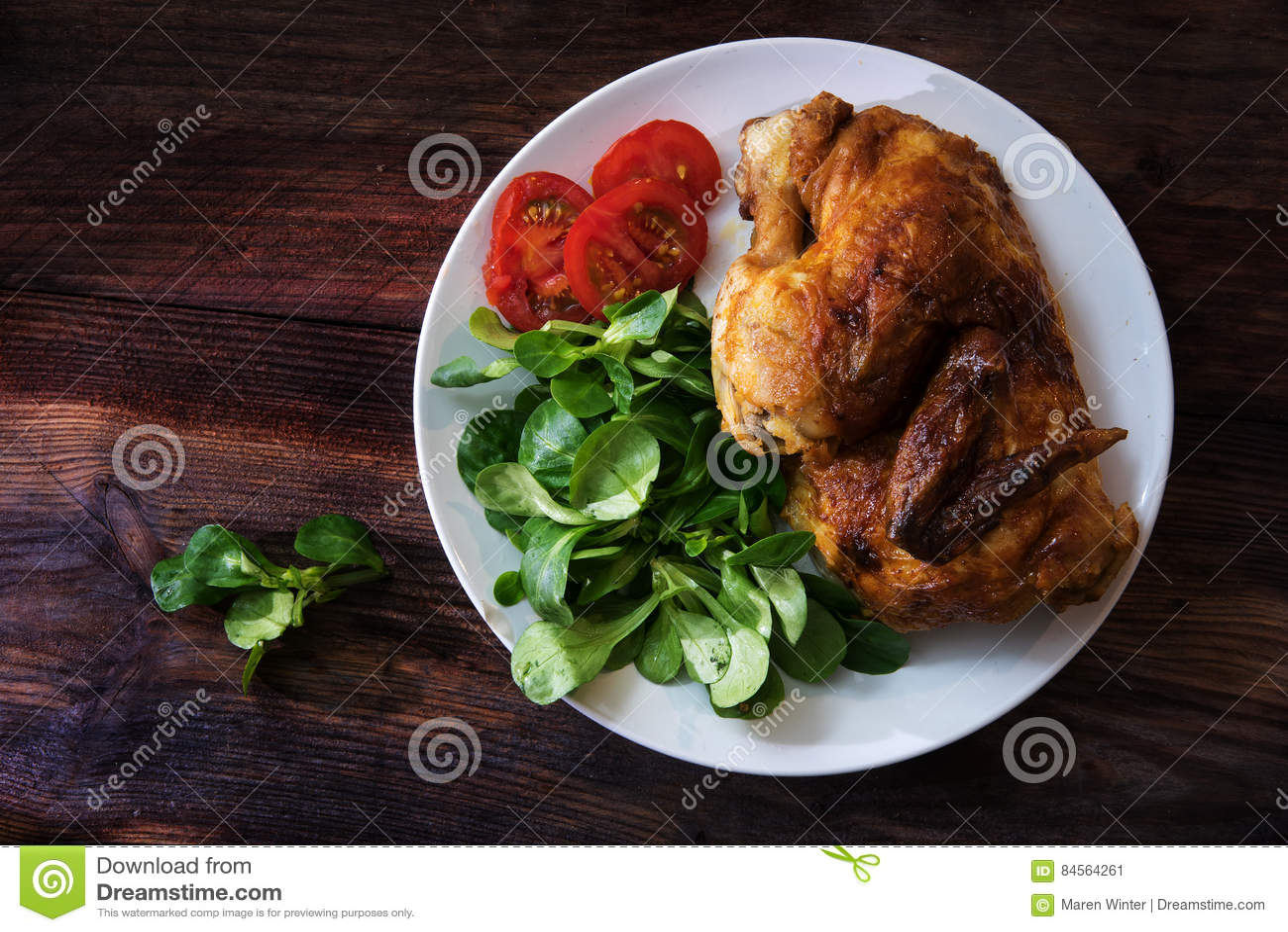 Meia galinha grelhada com tomates e salada de milho em um pla branco