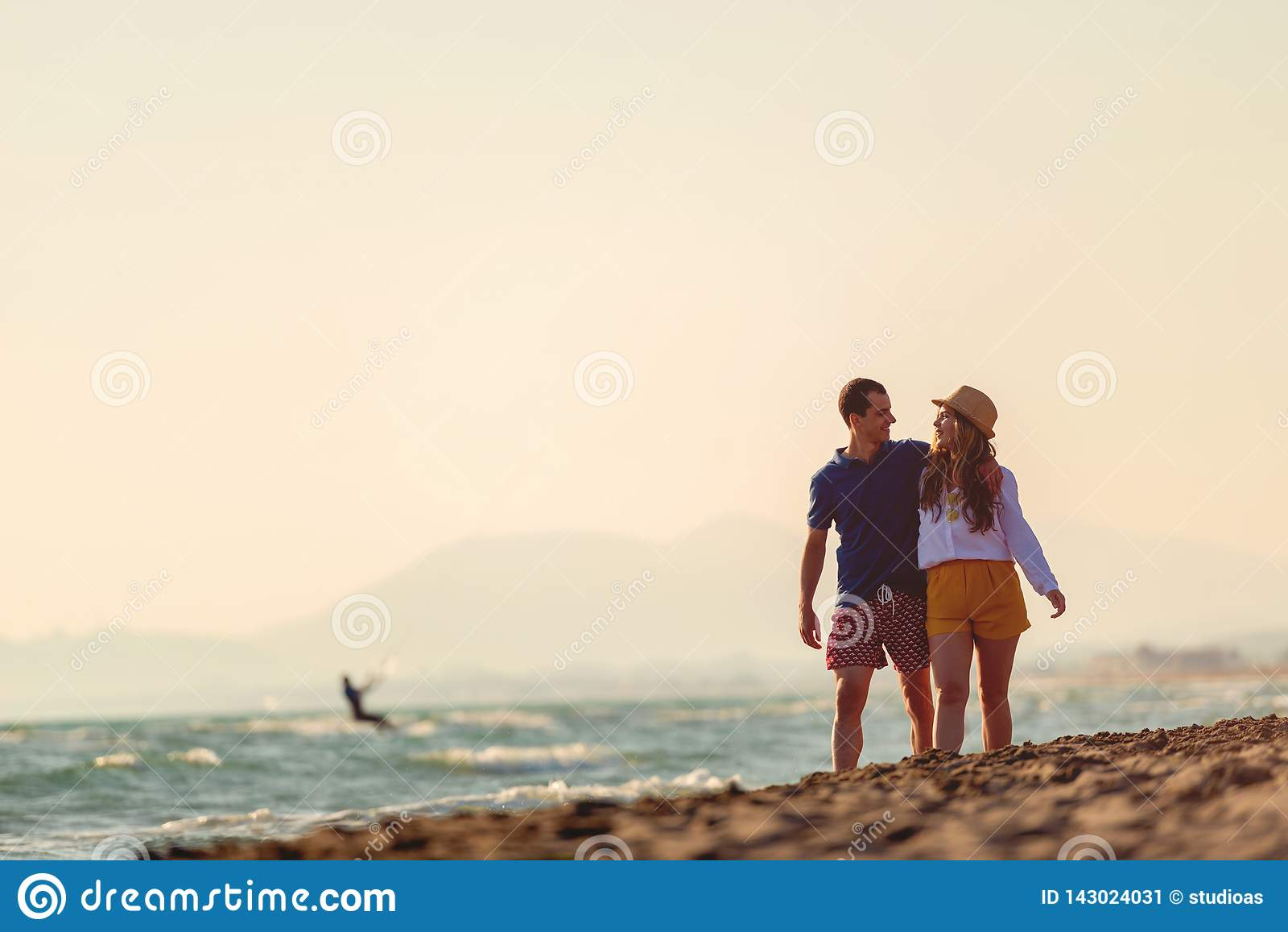 Meio rom?ntico feliz pares envelhecidos que apreciam a caminhada bonita do por do sol na praia