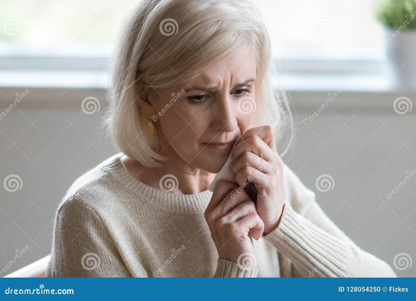 Meio virado mulher envelhecida que limpa o lo deprimido de sentimento de grito dos rasgos