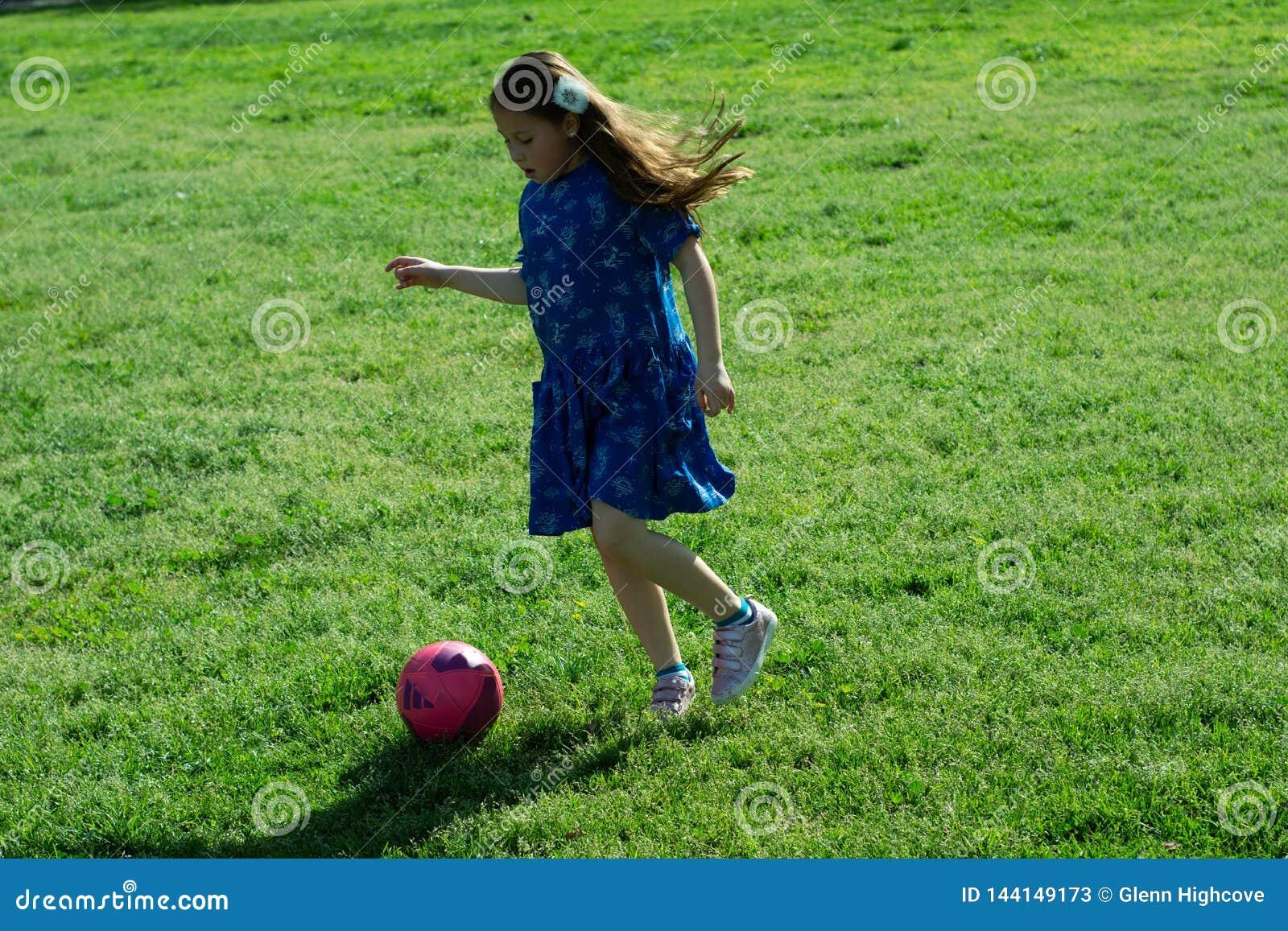 Meisje in Blauwe Kleding het schoppen voetbalbal op Groen Gras