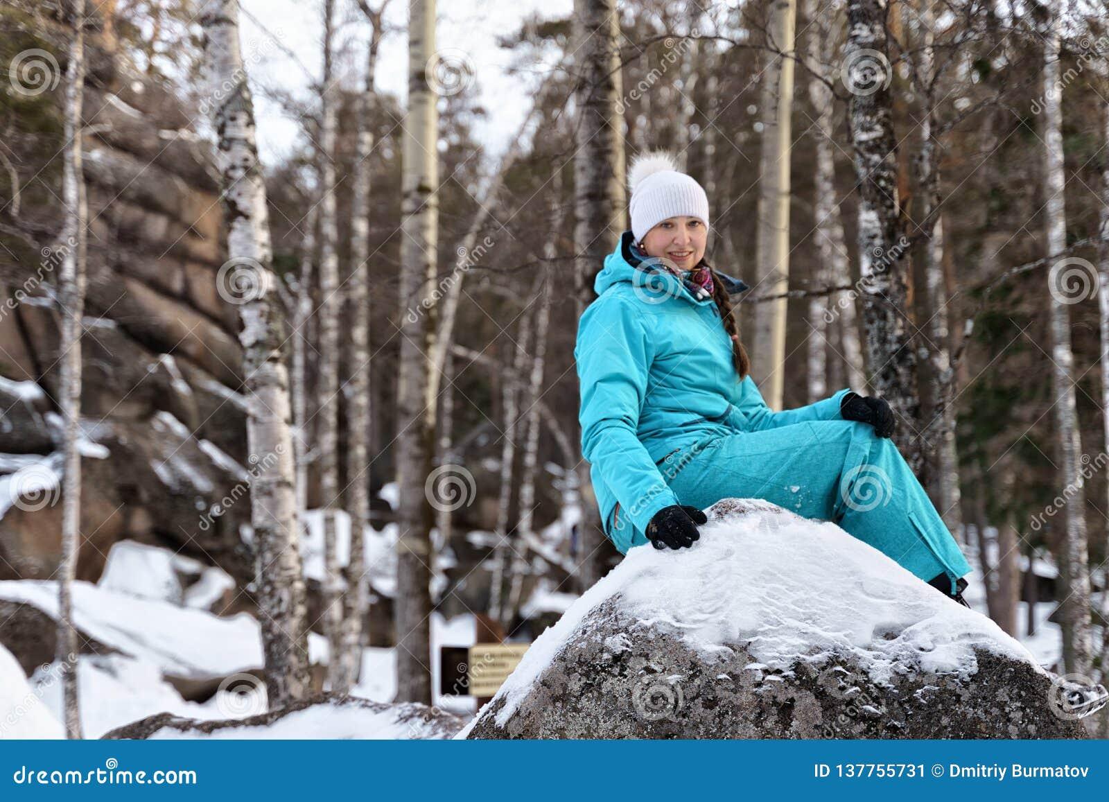 Meisje in blauwe sportkledingszitting op een grote kei op de aard op de achtergrond van rotsen in de winter