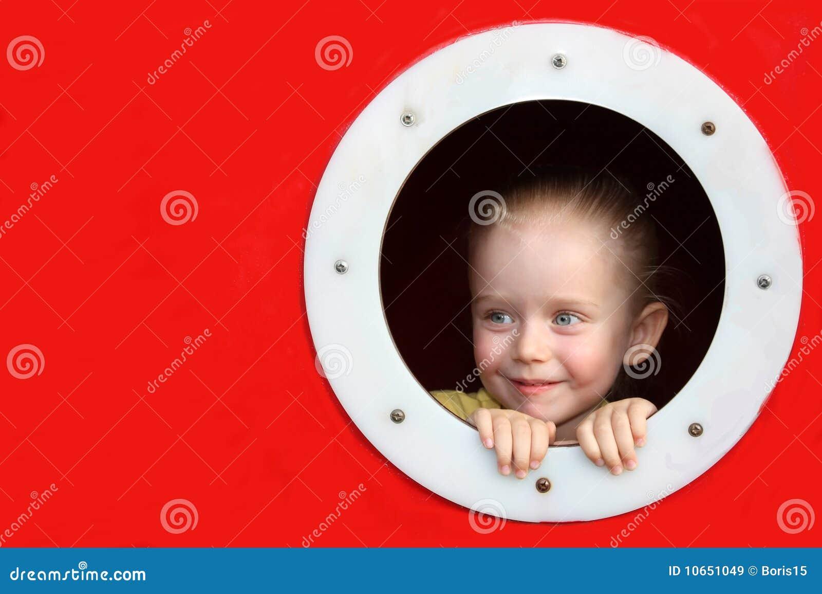 Meisje dat door cirkelvenster kijkt