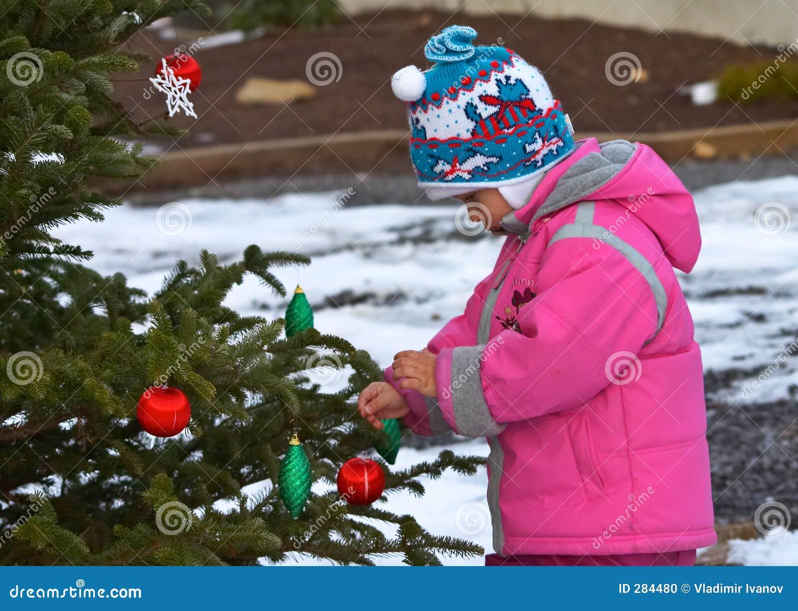 Meisje dat Kerstmisboom verfraait