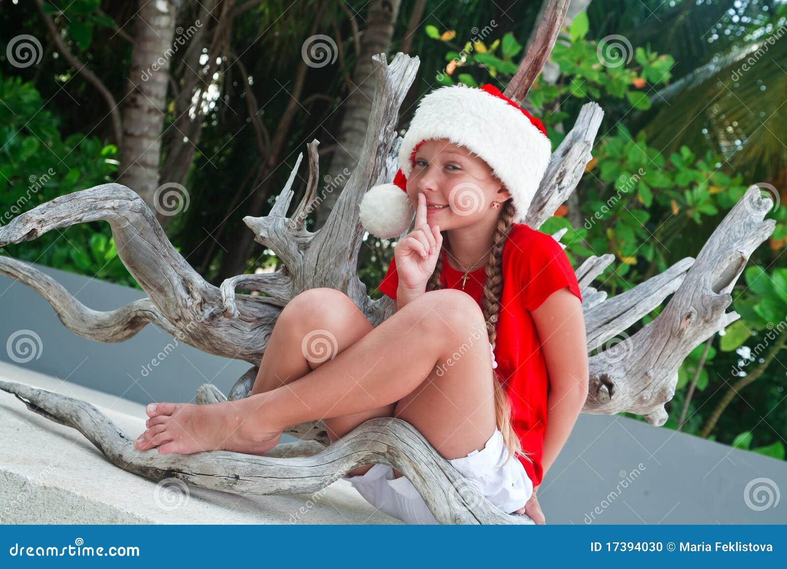 Meisje dat op de hoed van de Kerstman stiltegebaar maakt
