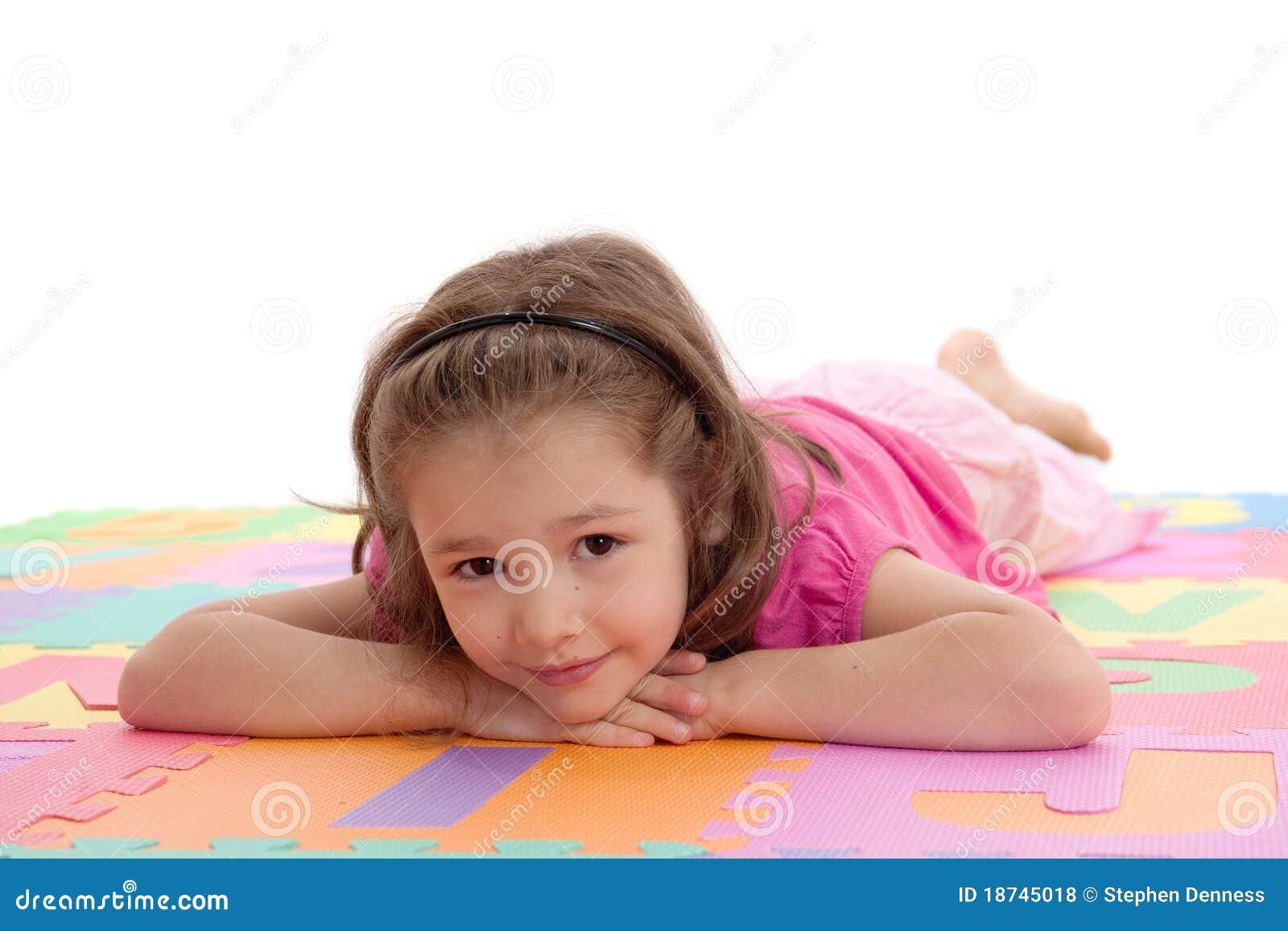 Meisje dat op de kleurrijke mat van de alfabetvloer rust
