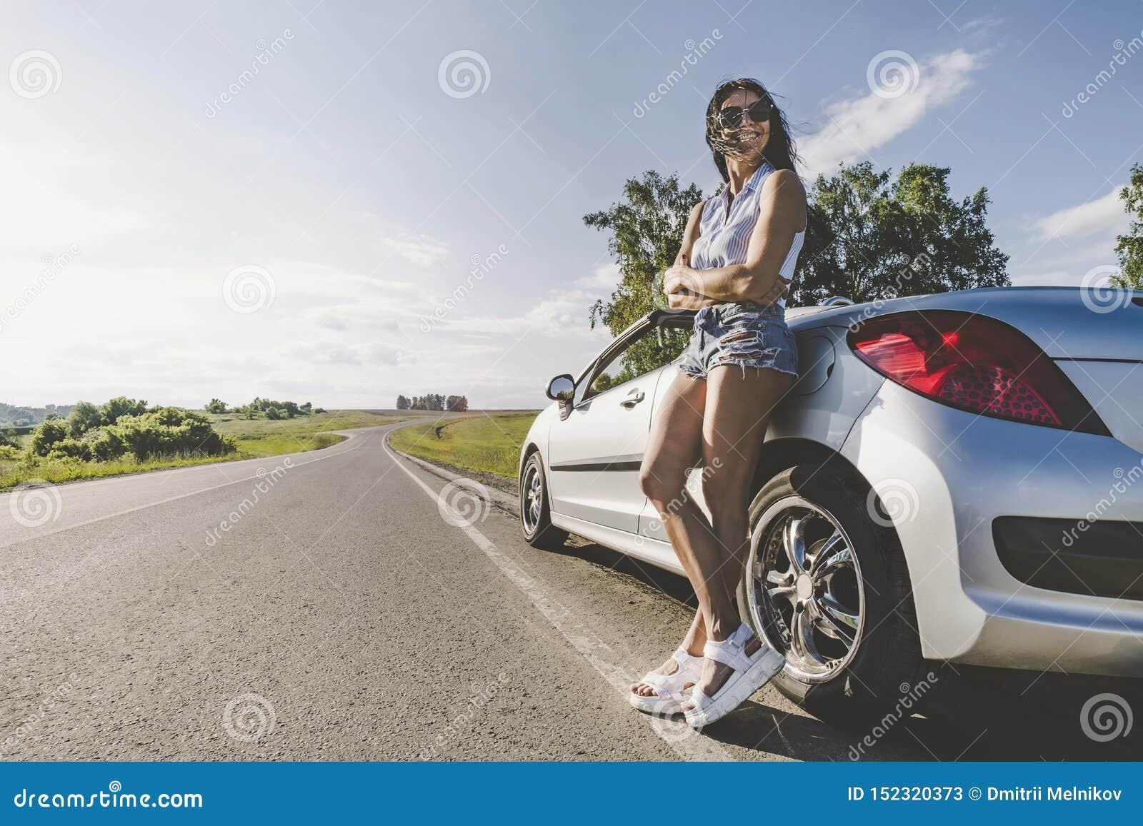 Meisje in de heldere zon op weg met cabriolet auto Het concept avontuur en alleen reis Wegreizen lift
