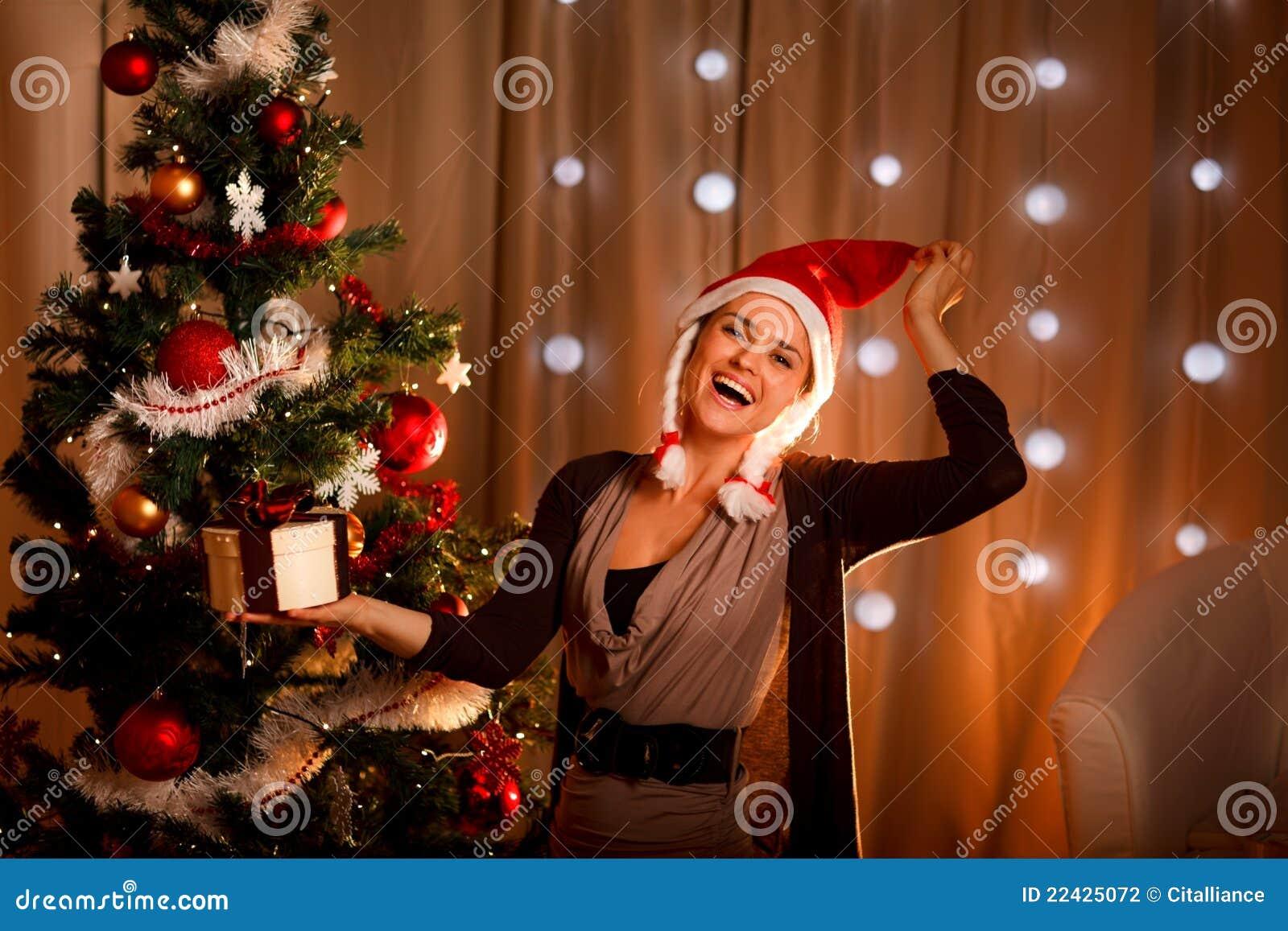 Meisje in de hoed van de Kerstman dichtbij Kerstboom met heden